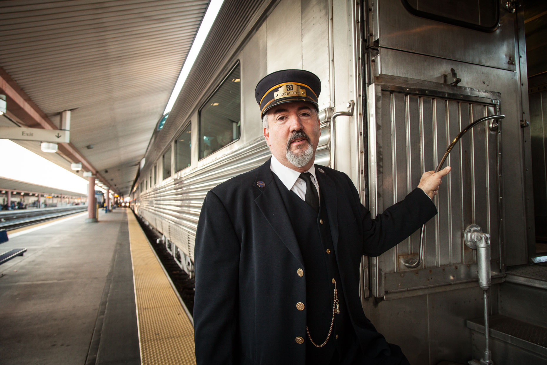 Portrait of train conductor standing near train doorway at Union Station in Los Angeles, California.