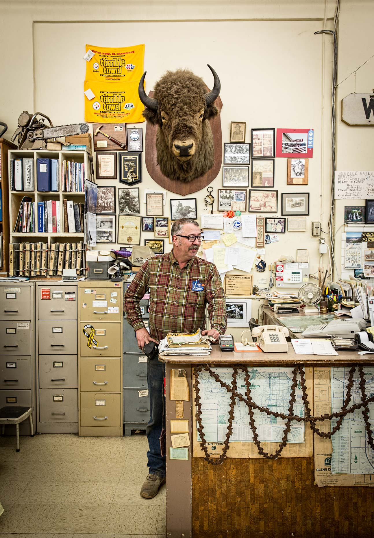 Portrait of man in cluttered hardware store under stuffed buffalo bison head on wall. Willows, California by David Zaitz