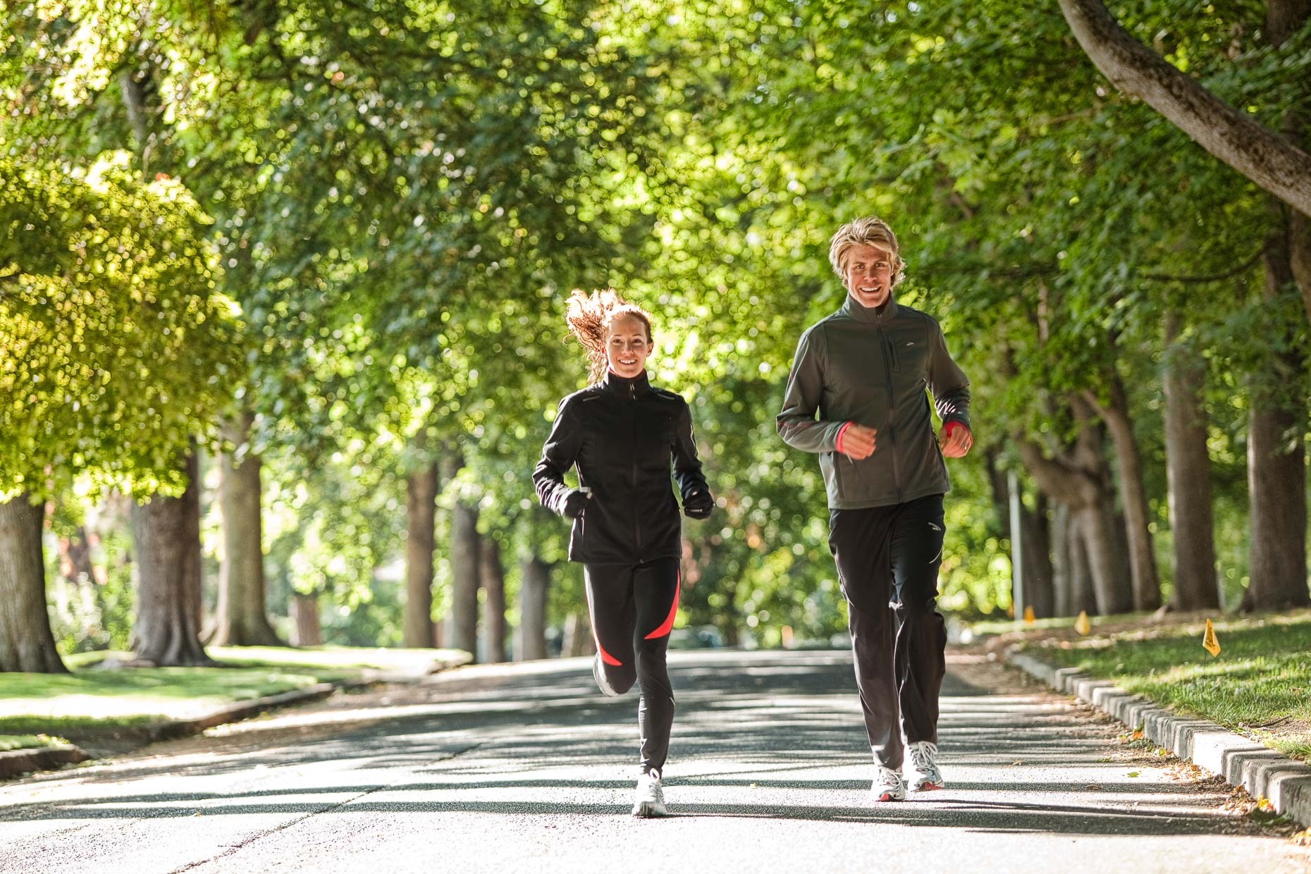 Man, woman, couple in running attire running on street road lined with trees by David Zaitz Photography.