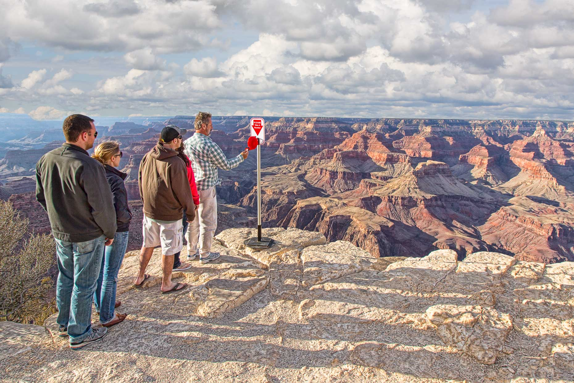 People wait in line to take a number from ticket machine at edge of the Grand Canyon.