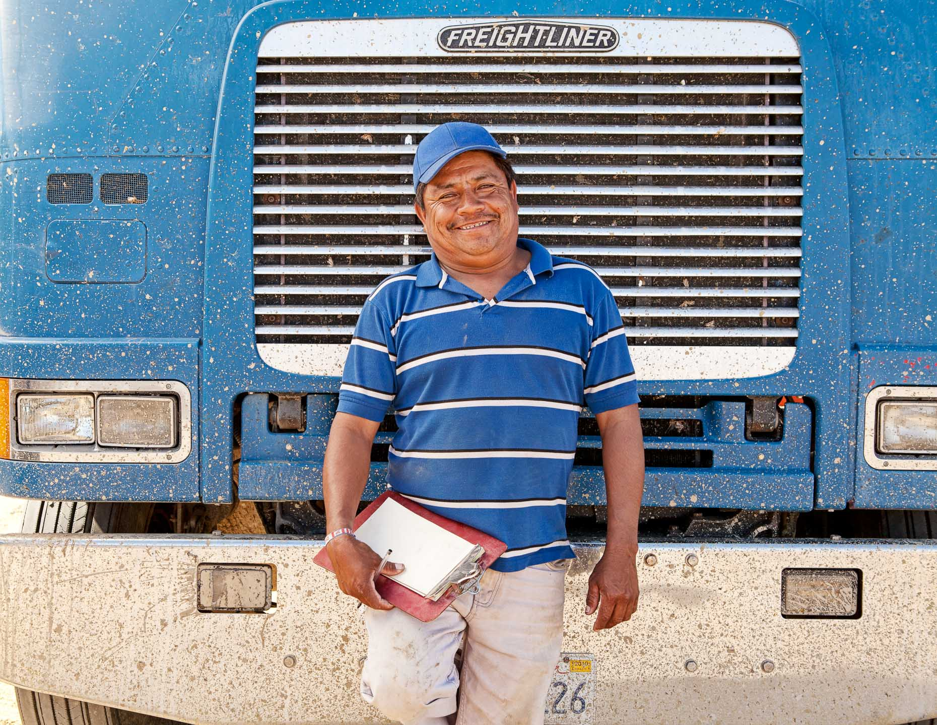Truck driver with white and blue striped shirt standing in front of chrome grill of big rig truck by David Zaitz.