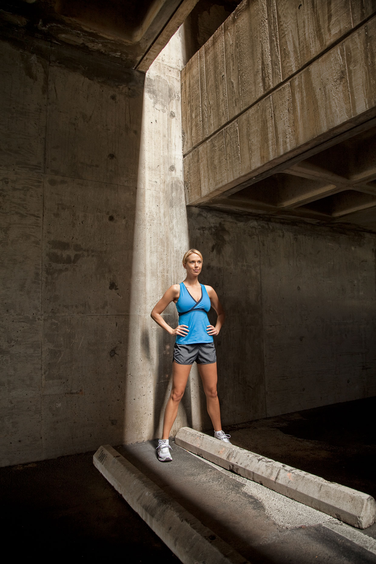 Female runner in blue running clothes rests in concrete parking garage with shaft of light on her by David Zaitz Photography.