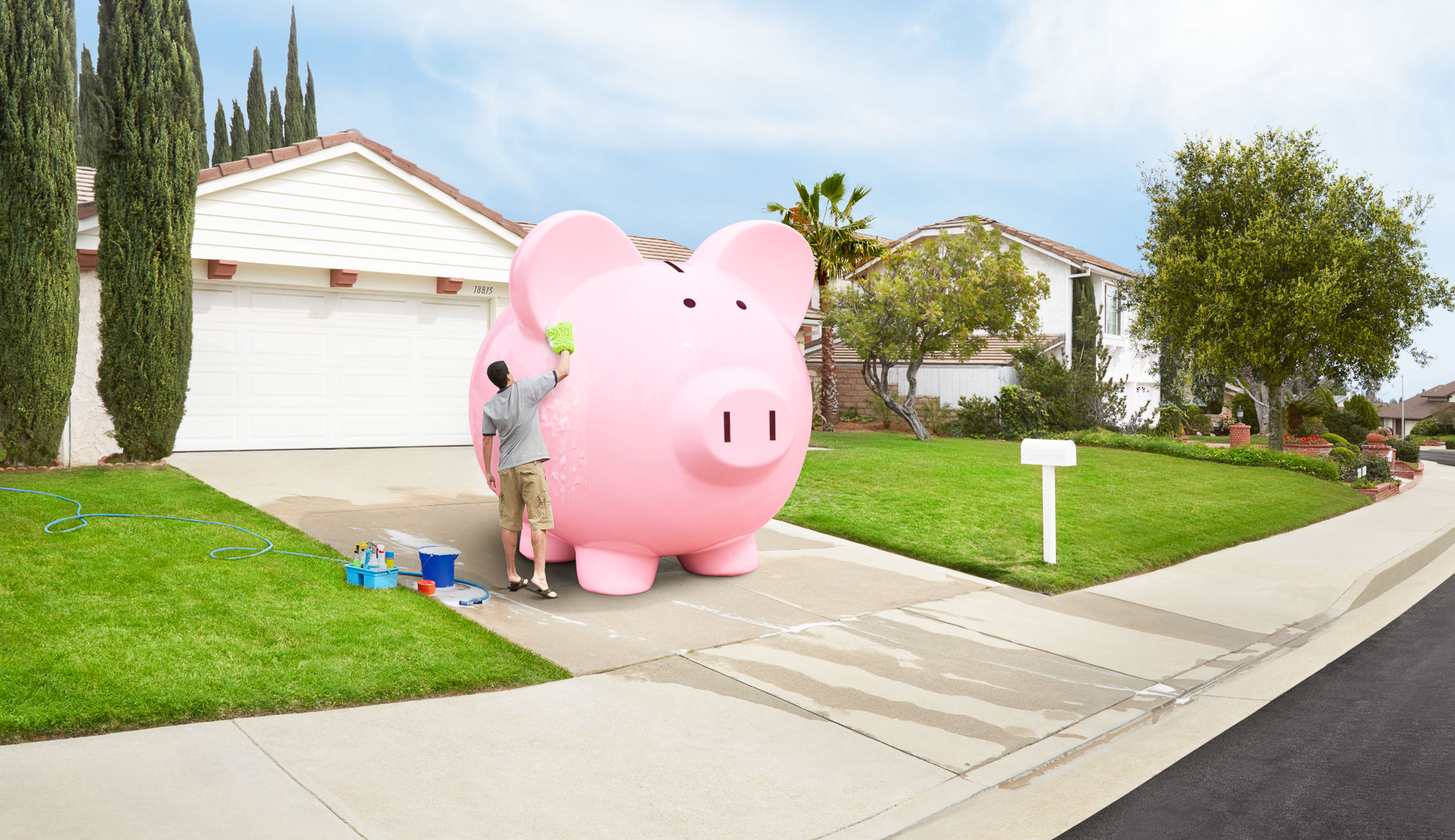 Man washing huge pink piggy bank in driveway of house. David Zaitz.