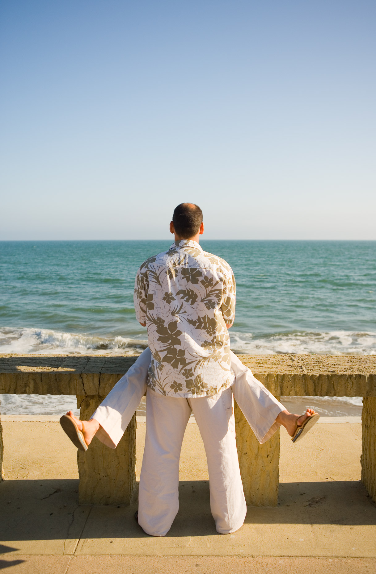 Man and woman at concrete railing overlooking ocean in Santa Barbara, California by David Zaitz