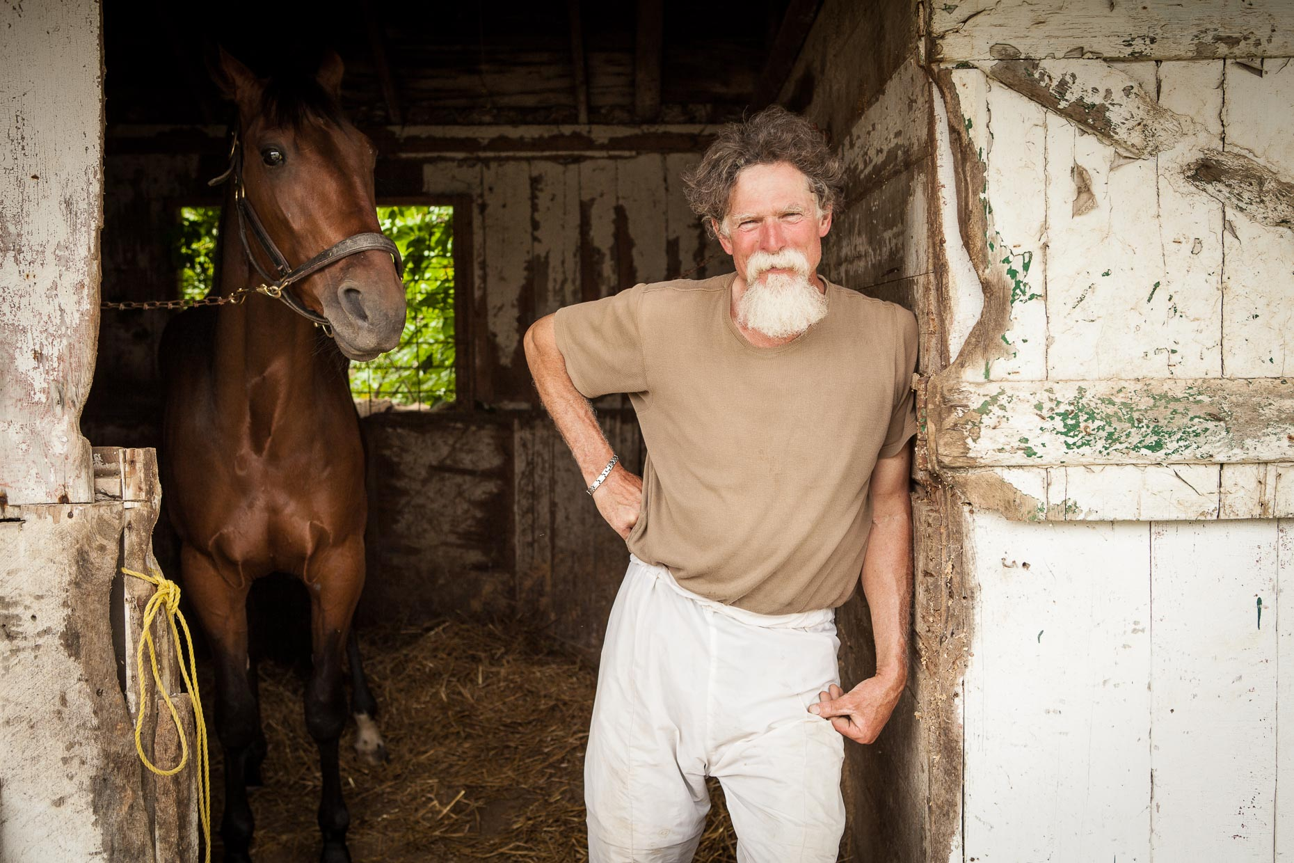Portrait of man with beard standing in horse stable with horse in background by David Zaitz