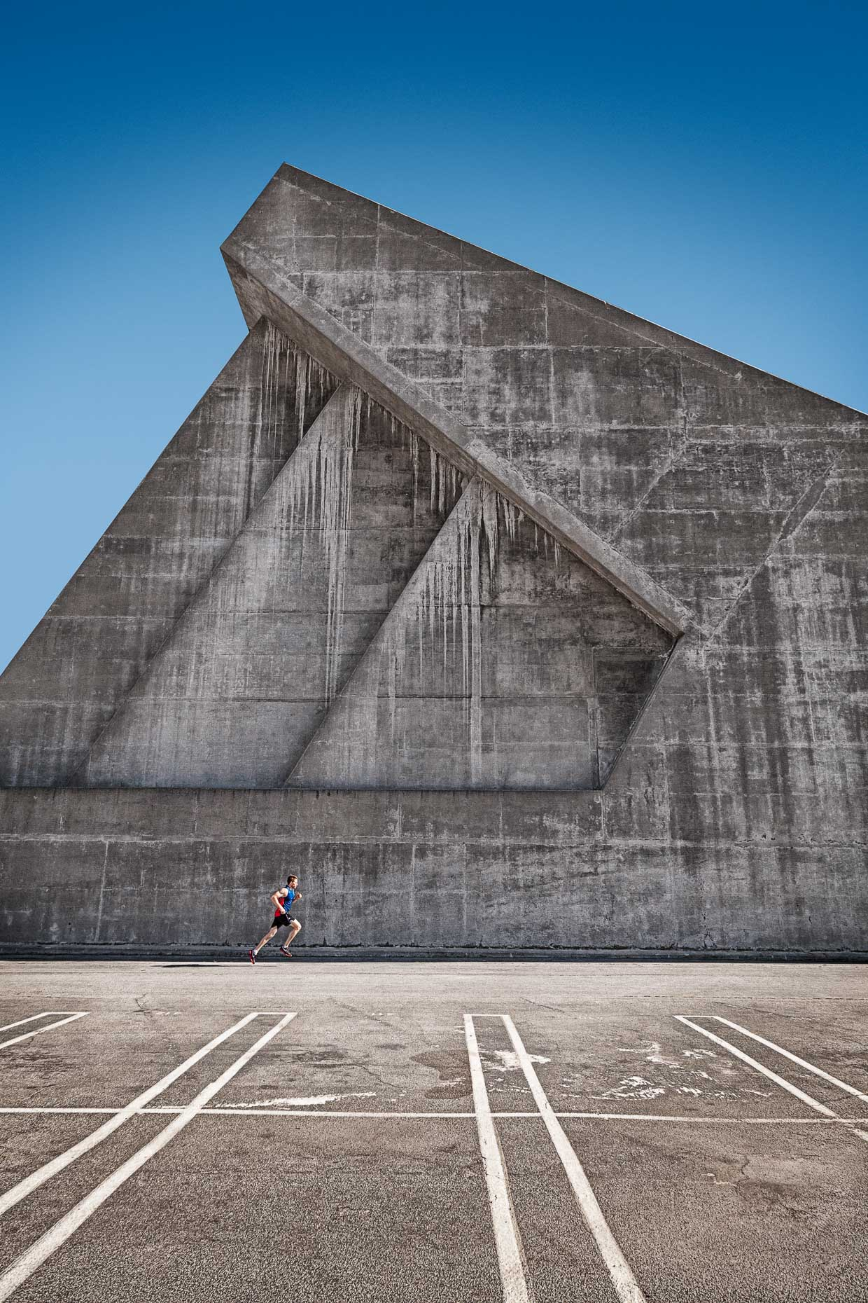 Man running against geometrically formed shaped concrete wall by David Zaitz Photography.