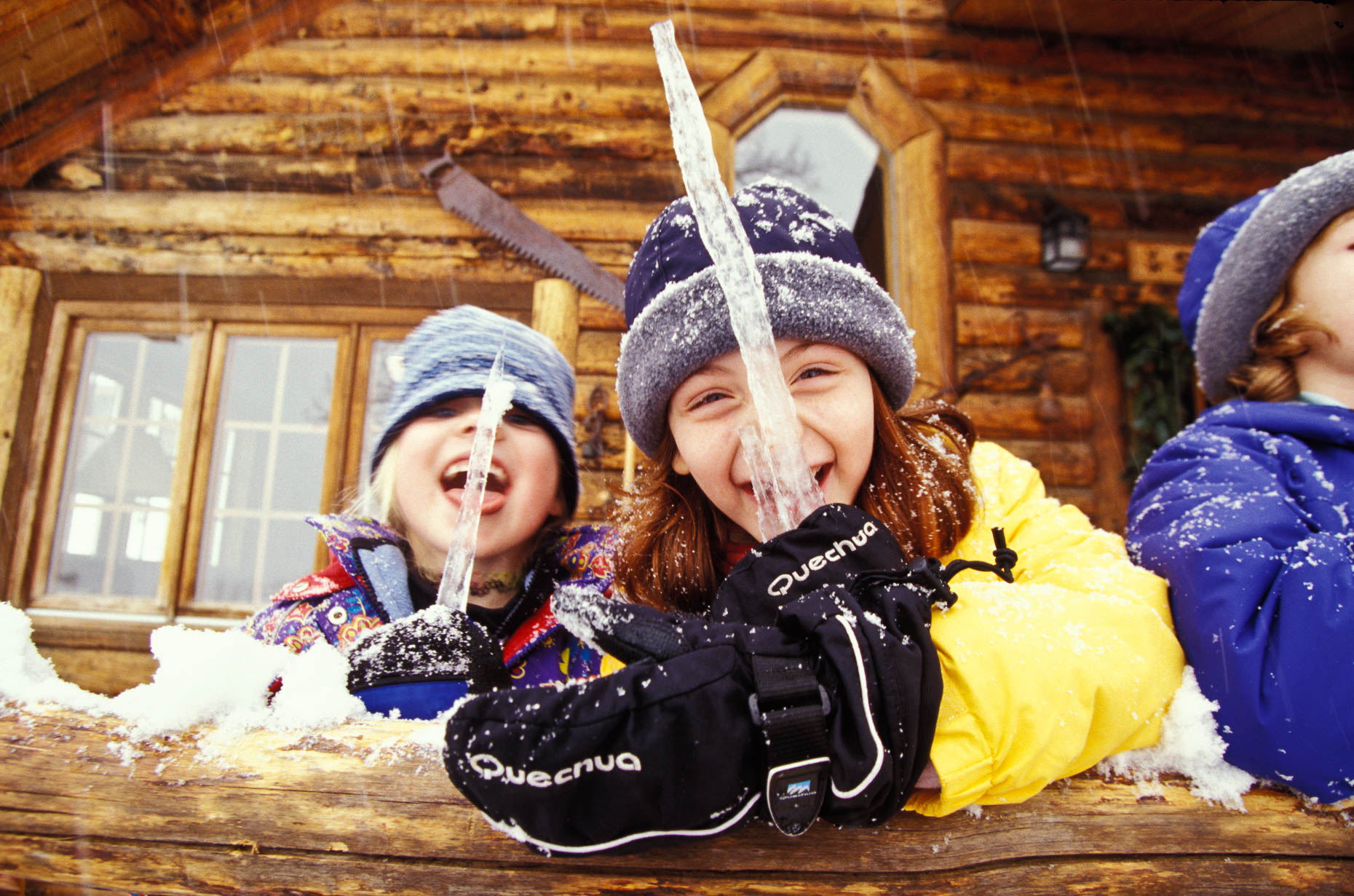 Girls licking icicle on porch of cabin at Vista Verde Ranch, Colorado by David Zaitz