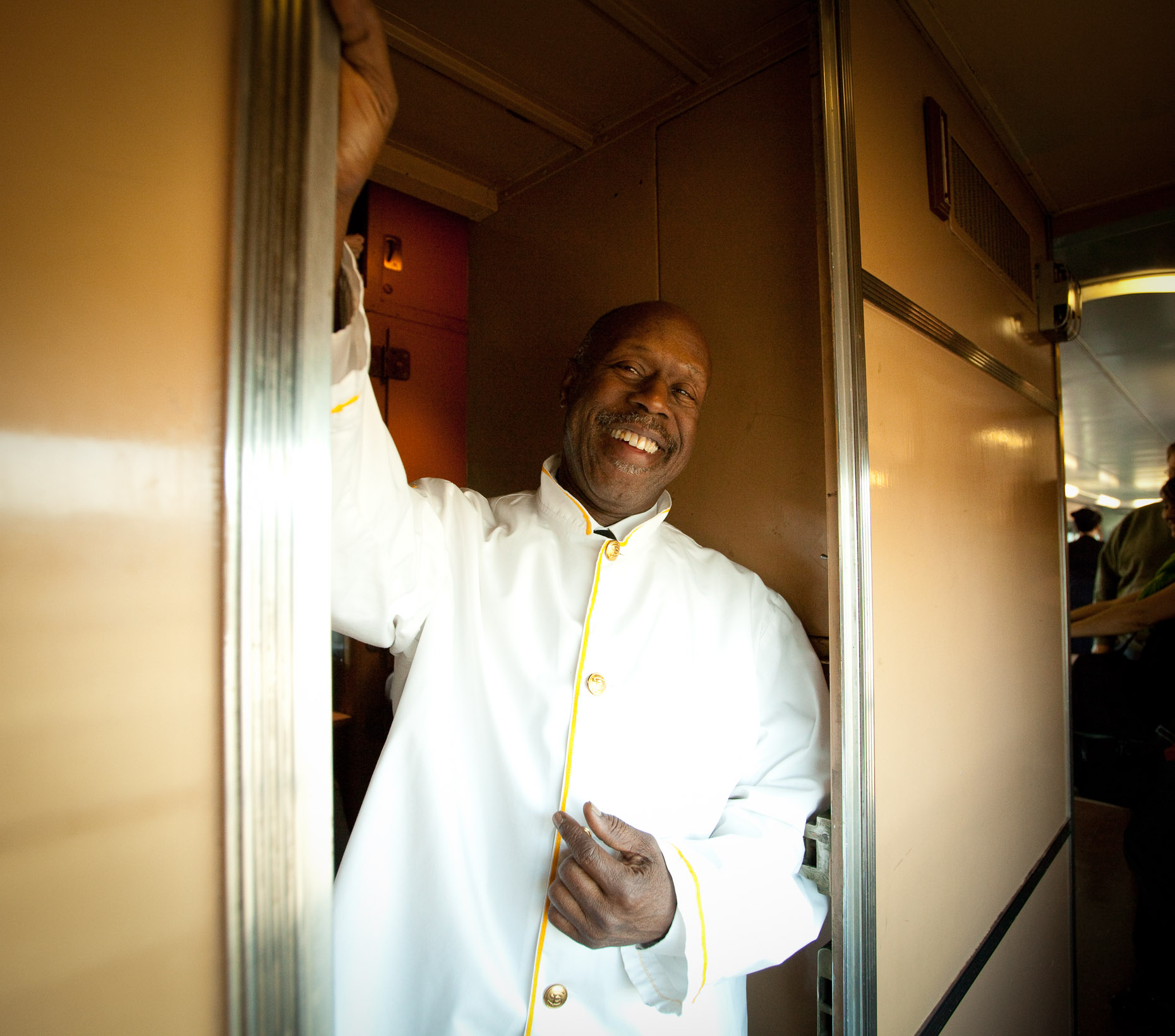 Environmental portrait of African American chef on train standing in kitchen doorway