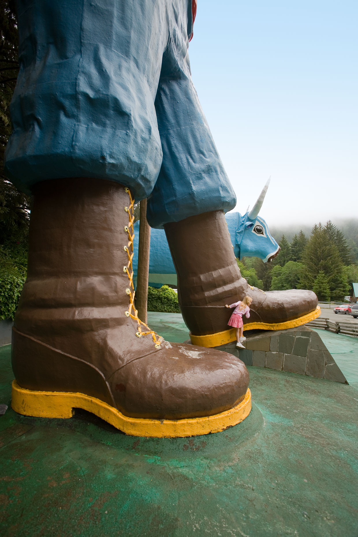 Girl climbs on large boot which is part of a statue of Paul Bunyan at roadside attraction in Klamath, California. Trees of Mystery by David Zaitz