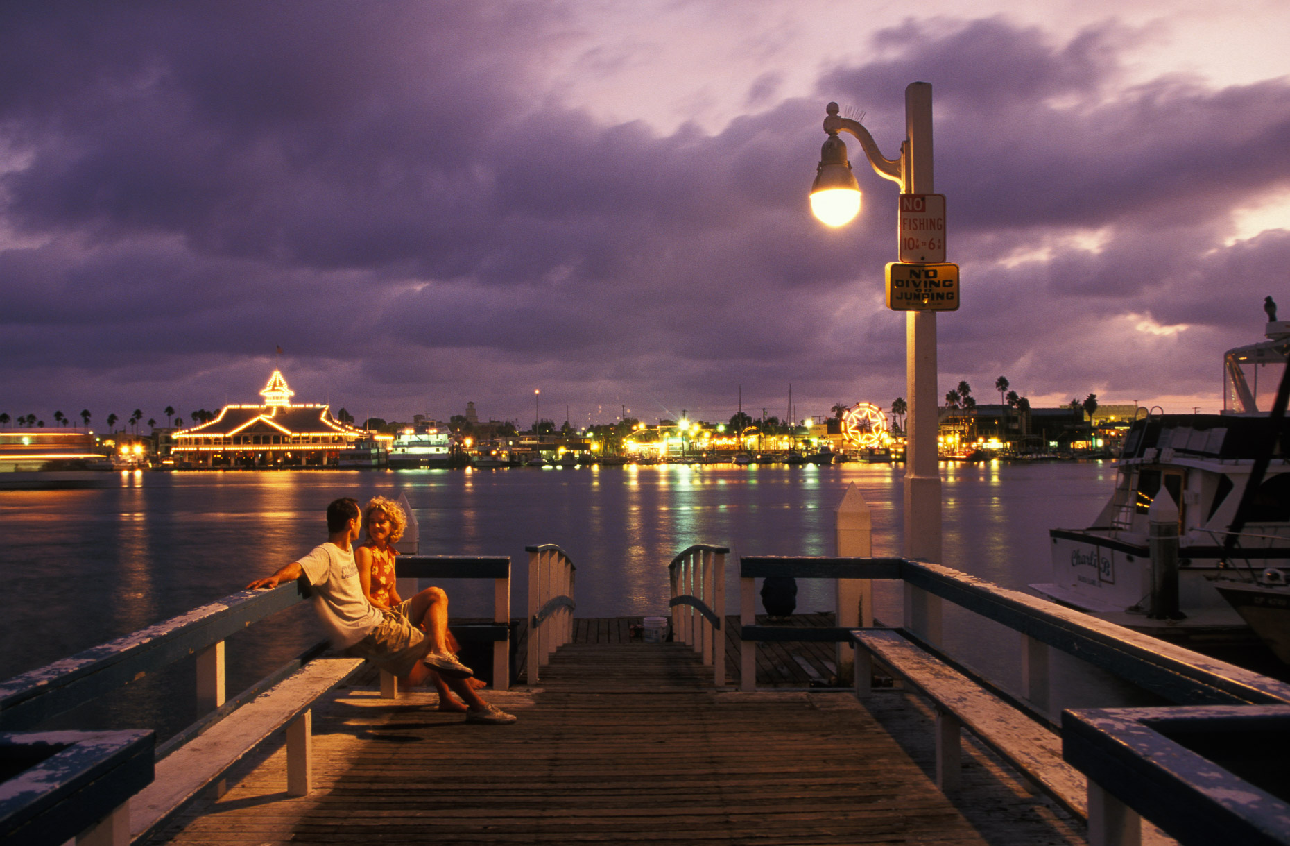 Man and woman sitting on bench on pier with sunset in background by David Zaitz.