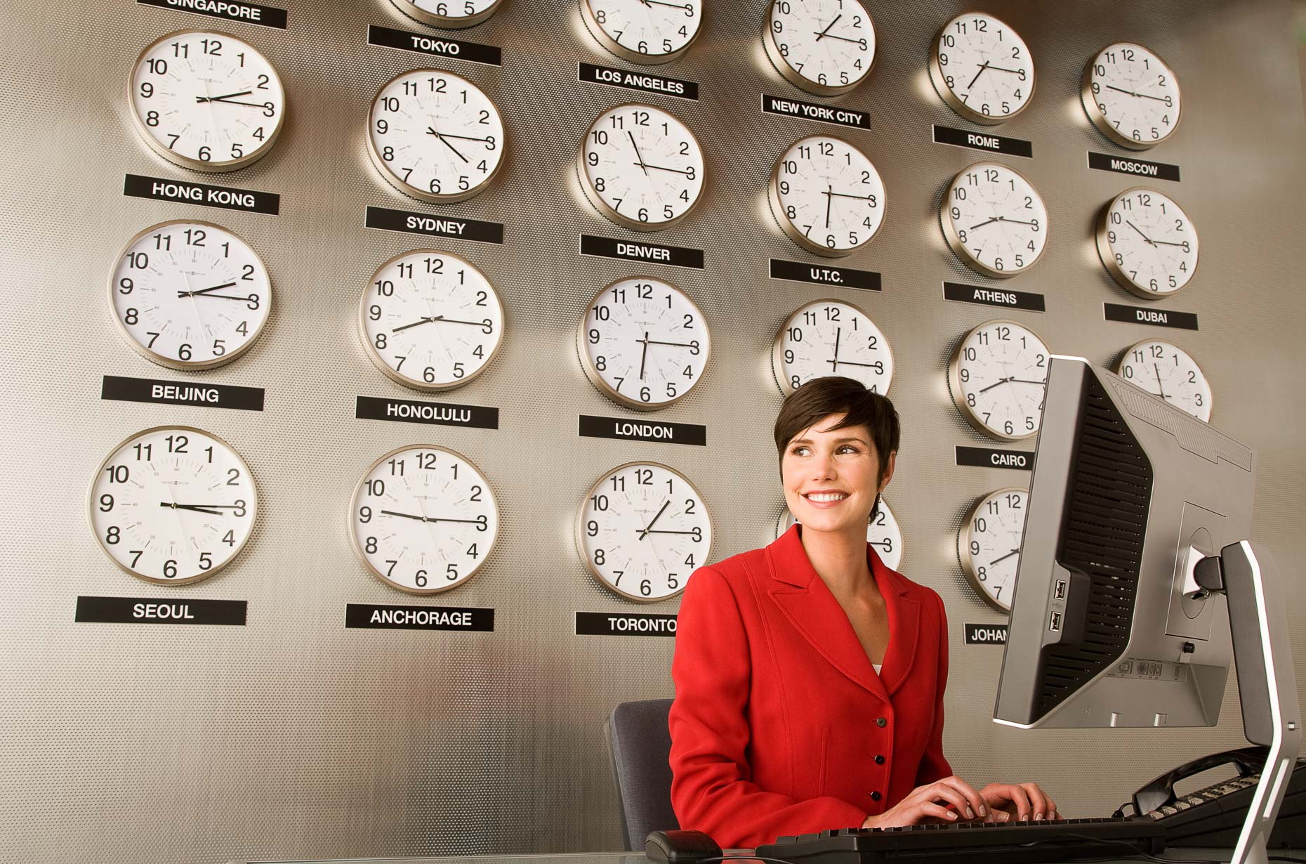 Woman in red dress working at computer with wall of clocks with various international times on them. Corporate, business. David Zaitz Photography.