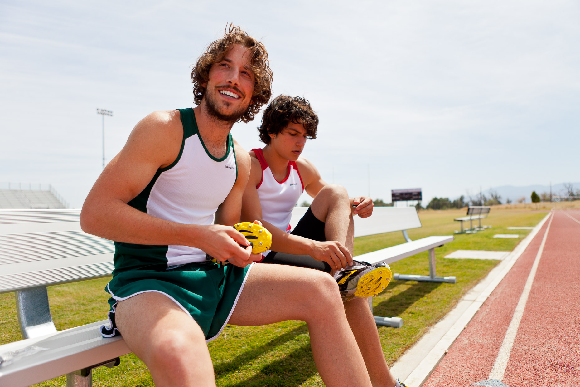 Male runners sitting on track field bench adjusting cleats on shoes in Palm Springs, California by David Zaitz Photography.