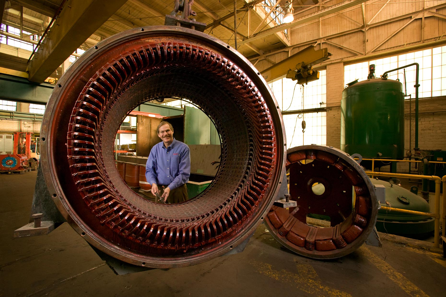Environmental portrait of businessman framed by electric motor part in factory by David Zaitz