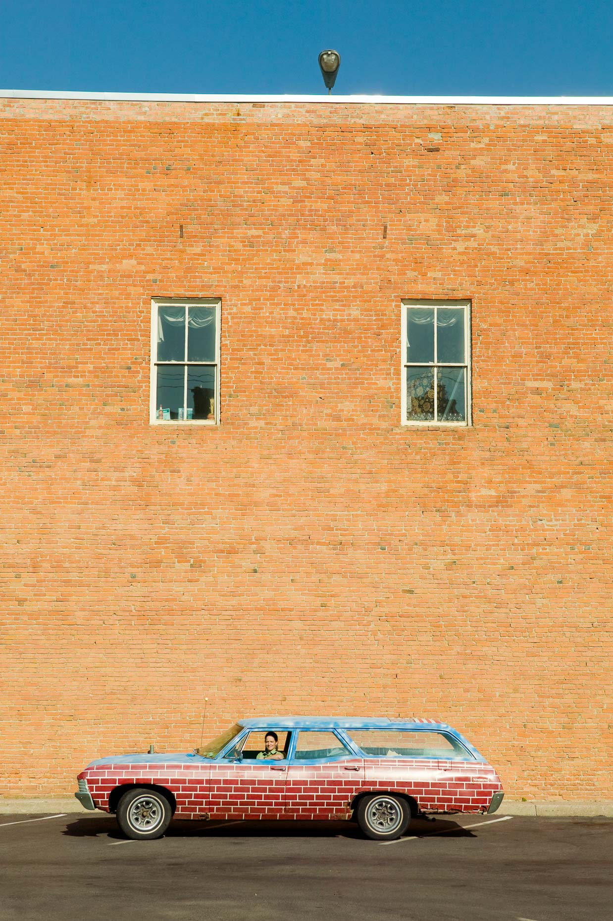 Portrait of woman in station wagon vehicle car painted with brick pattern in front of brick wall in Missoula, Montana by David Zaitz