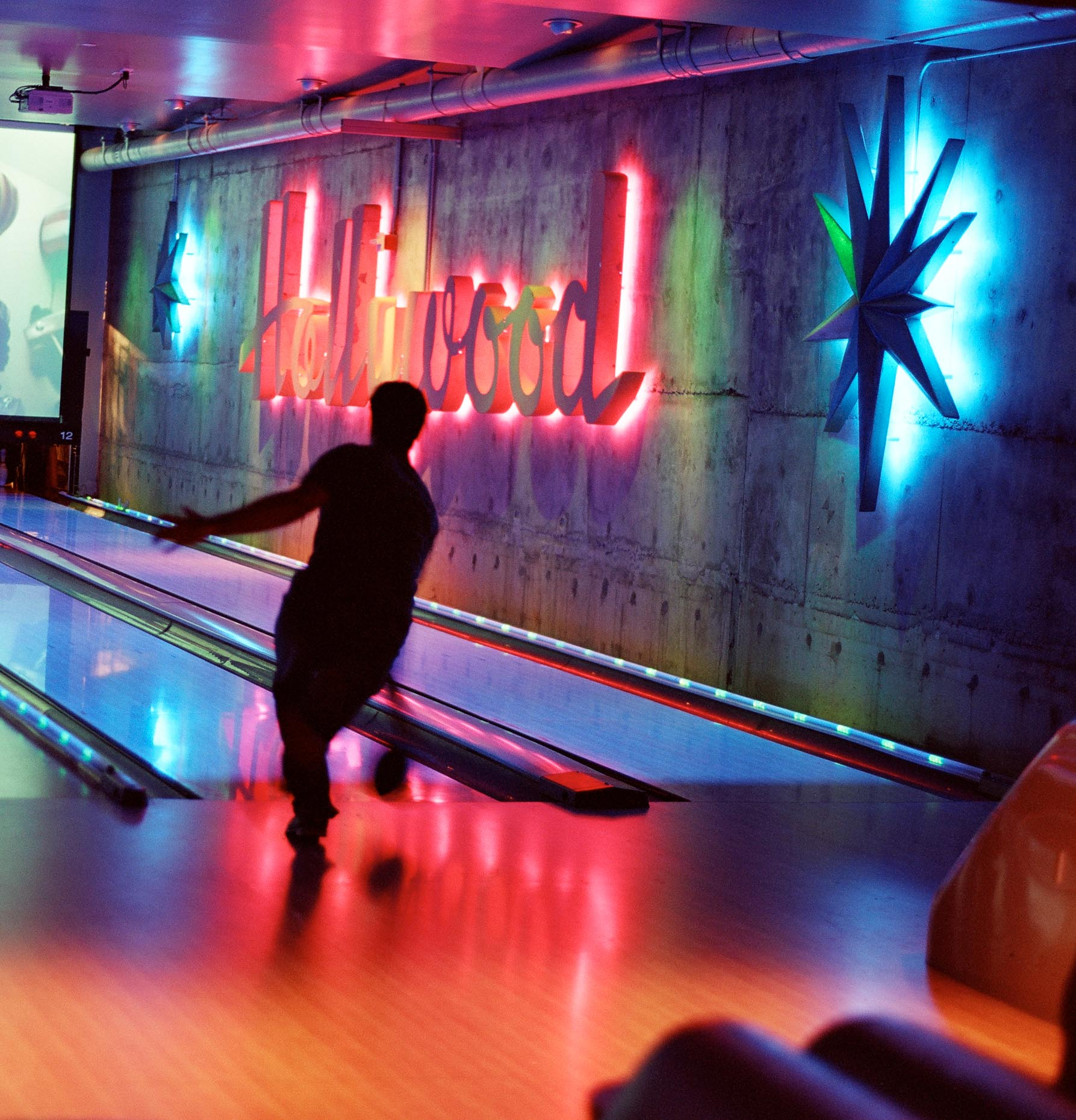 Man bowling in bowling alley with HOLLYWOOD sign on wall by David Zaitz