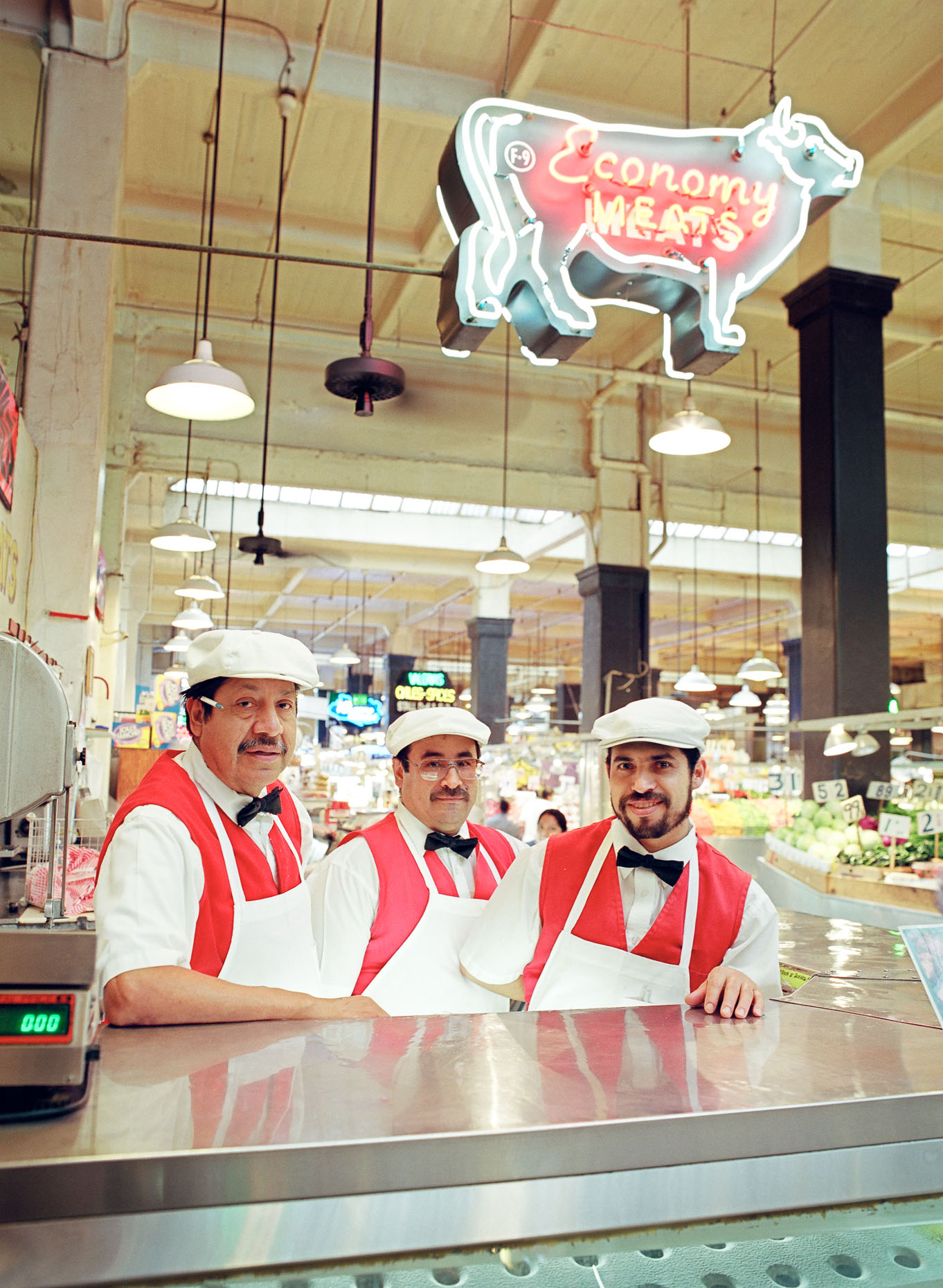 Environmental portrait of three meat butchers wearing aprons at meat market in Grand Central Market in Los Angeles, California with neon ECONOMY MEATS sign overhead.
