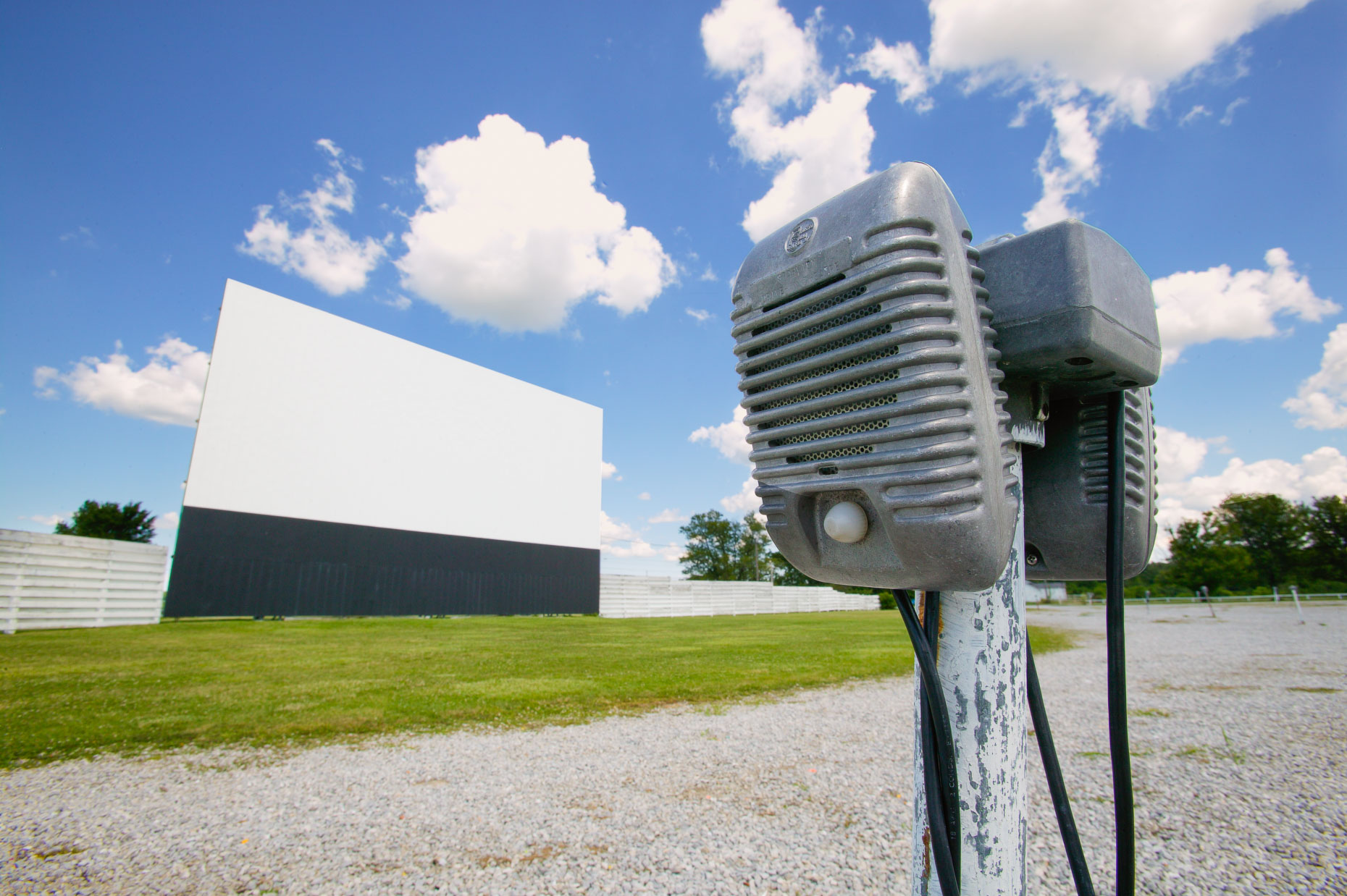 Speakers at drive in movie theater with movie screen in background in Ohio by David Zaitz