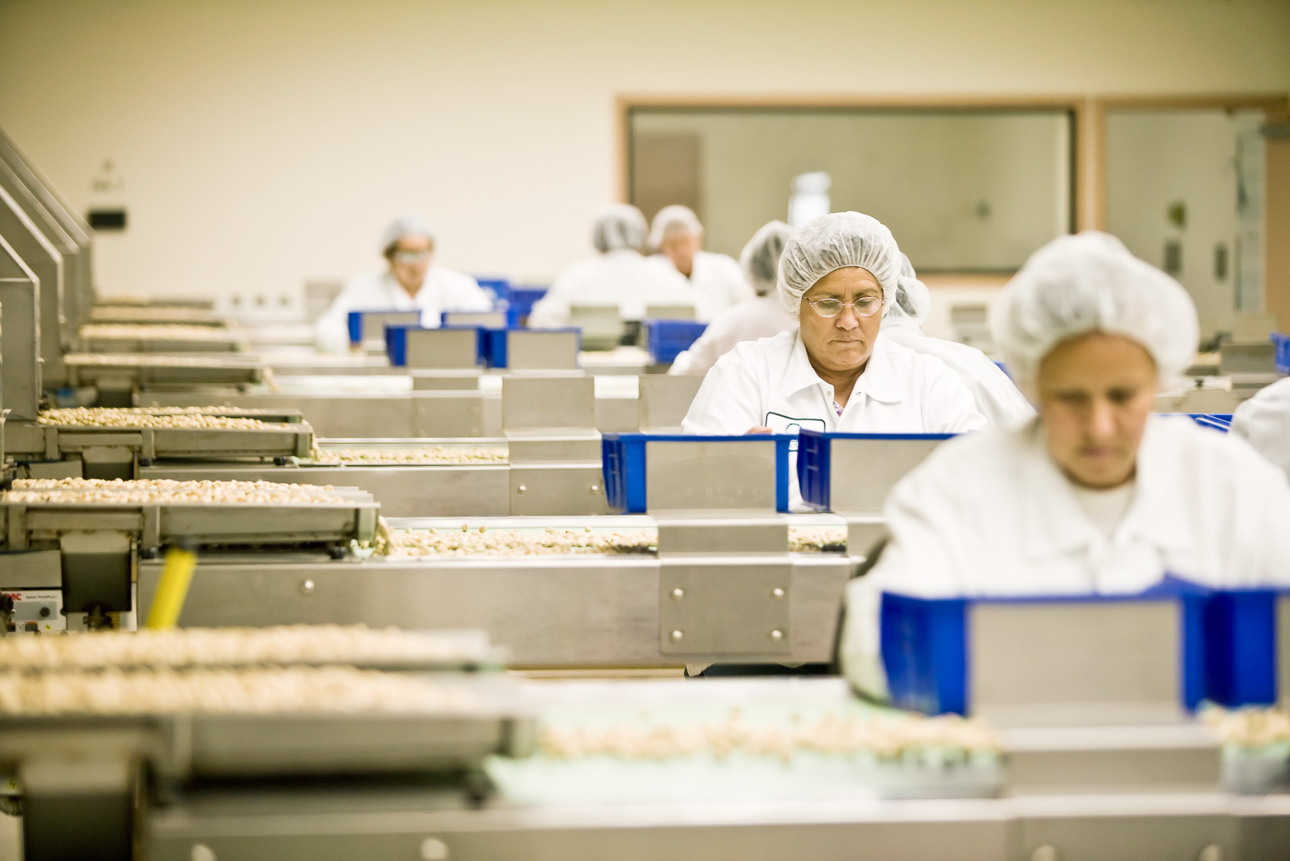 Women sorting pistachios in processing plant. Industrial, agriculture. David Zaitz Photography.