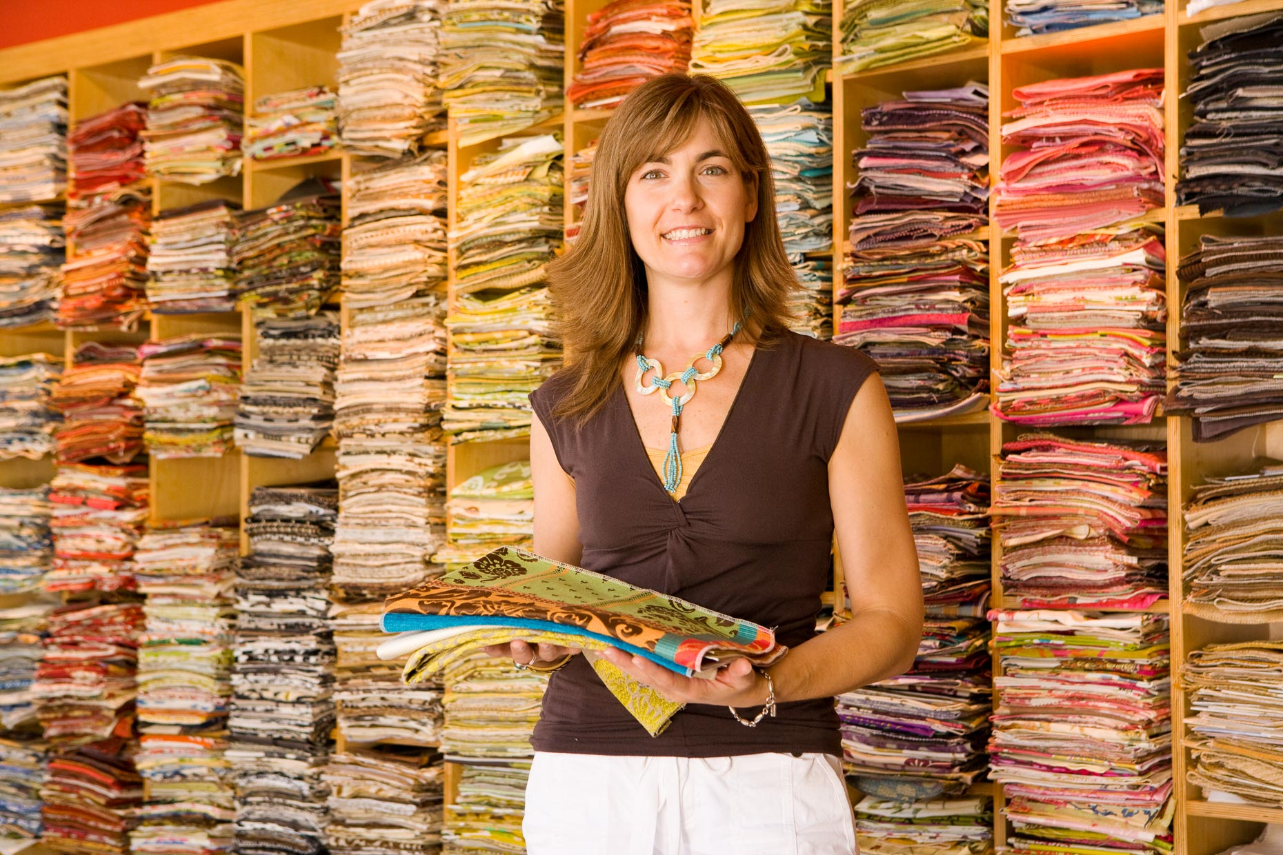Portrait of woman holding fabric samples swatches at interior design firm in Culver City, California by David Zaitz