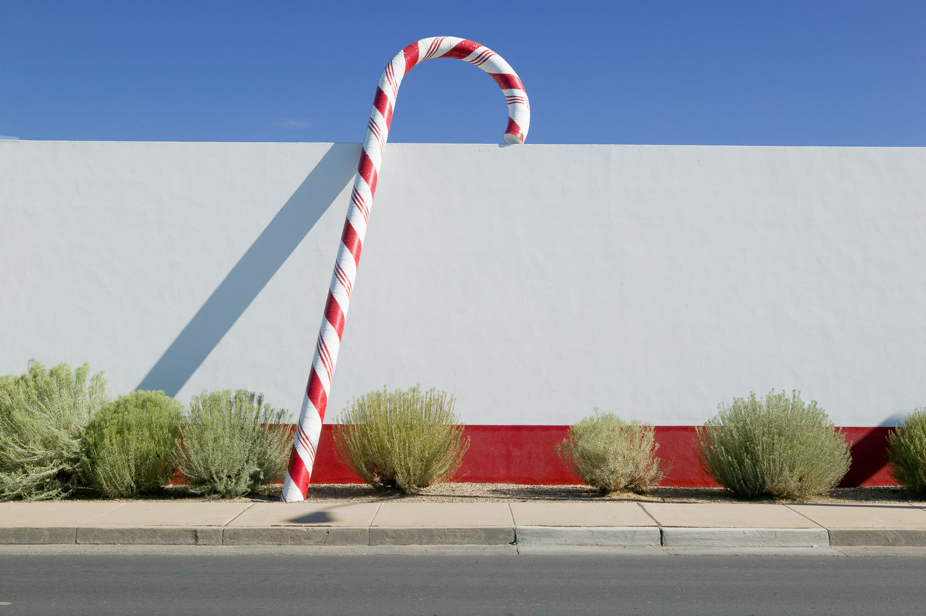 Large candy cane prop against white wall of commercial building by David Zaitz