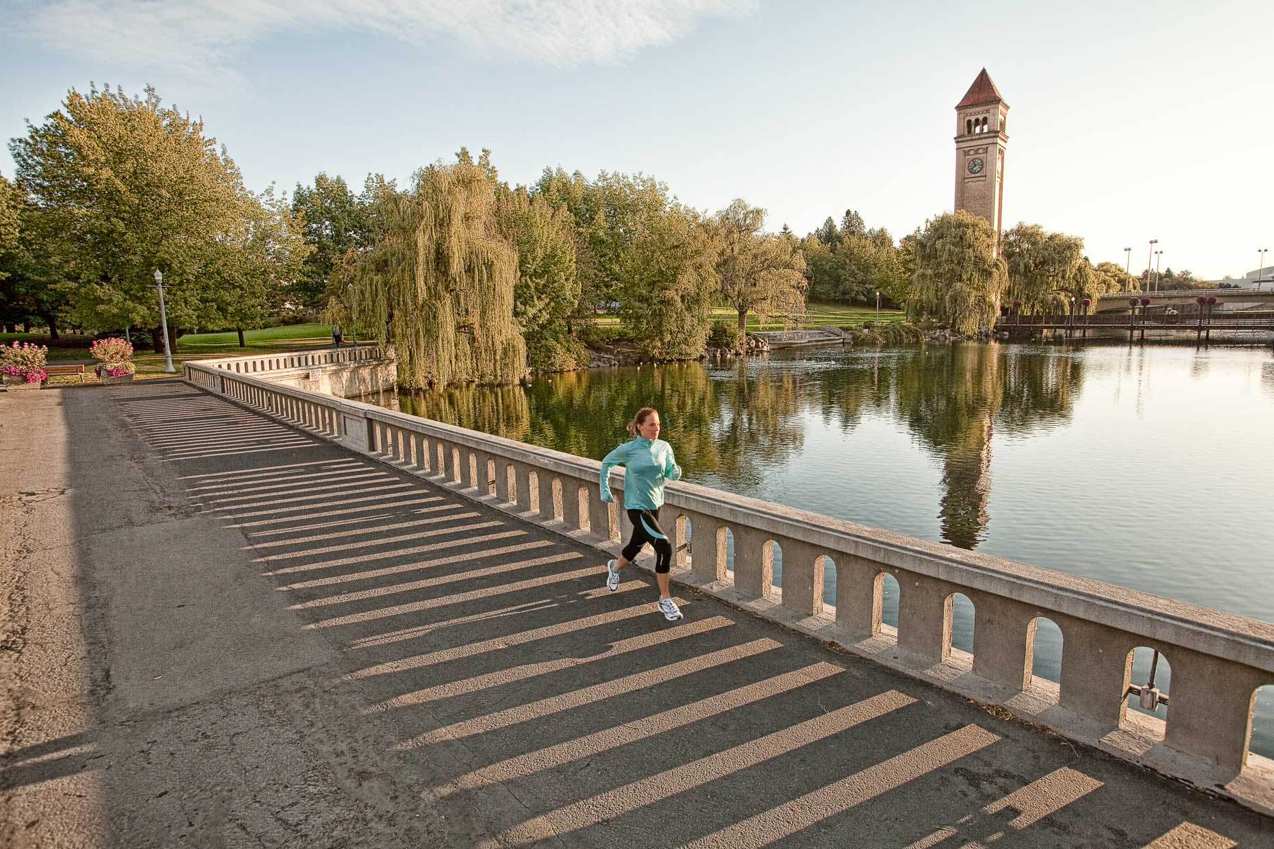 Woman running on bridge over lake with clock tower in background by David Zaitz Photography.