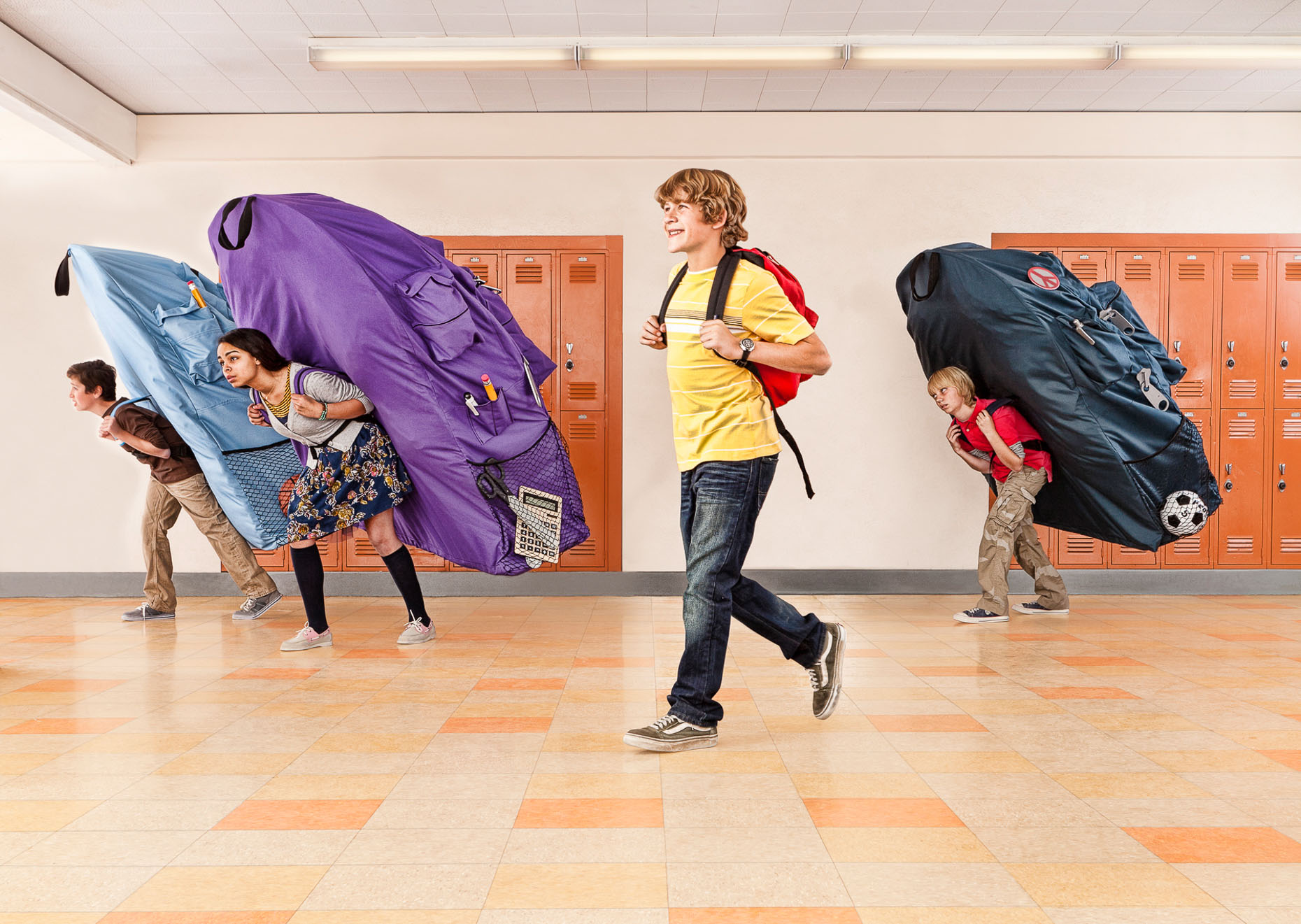 boy with normal sized book bag is smiling while other students are burdened with oversized book bags by David Zaitz
