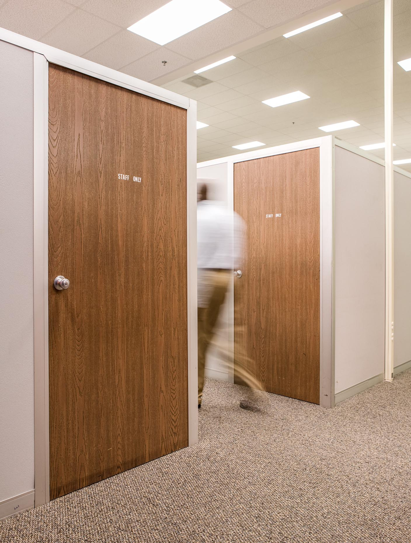Man walking in office hallway with OFFICE sign on door. Corporate. David Zaitz Photography.