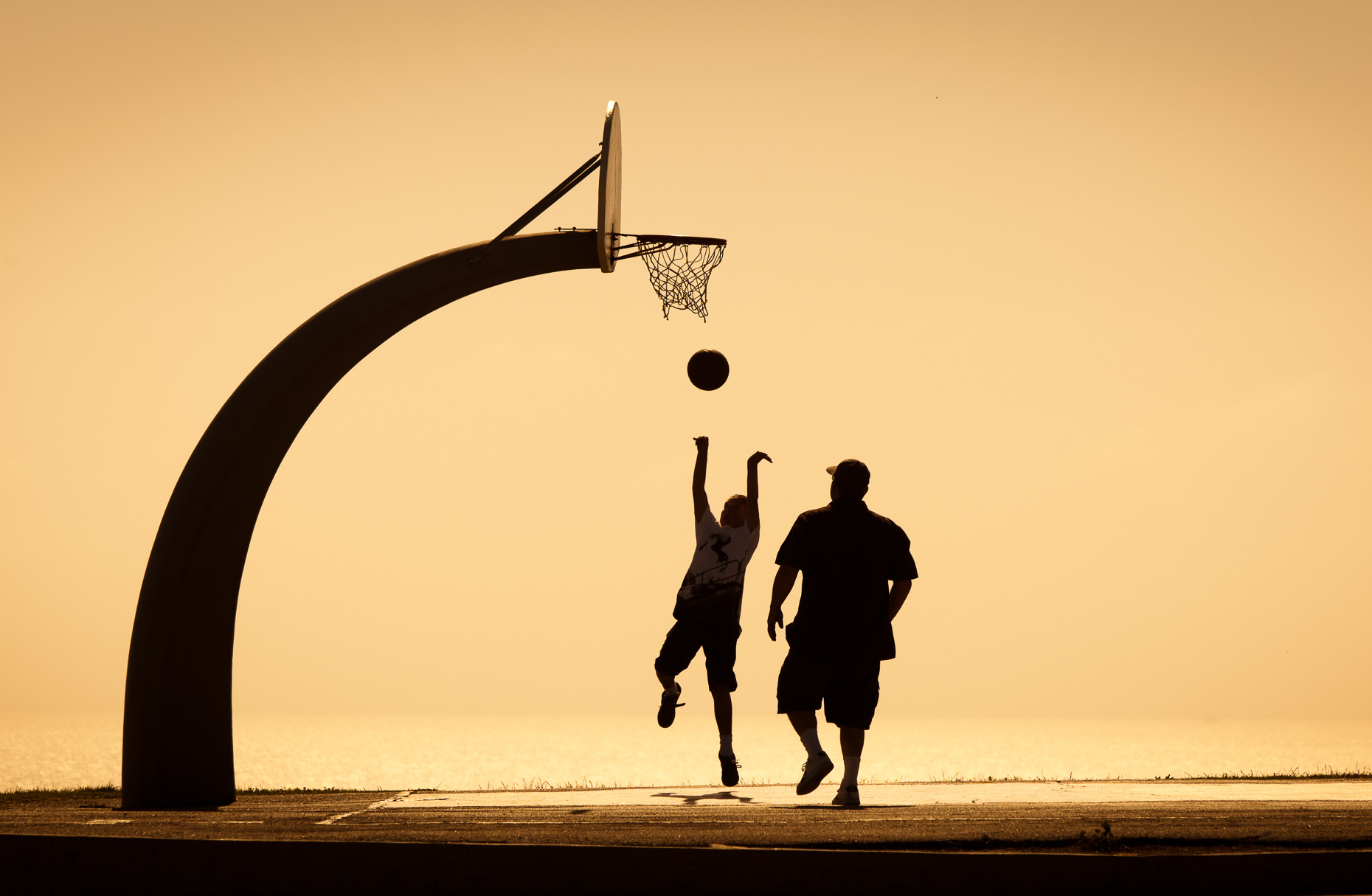 Silhouette of people playing basketball on court with sunset sky in background. Fitness. David Zaitz Photography.