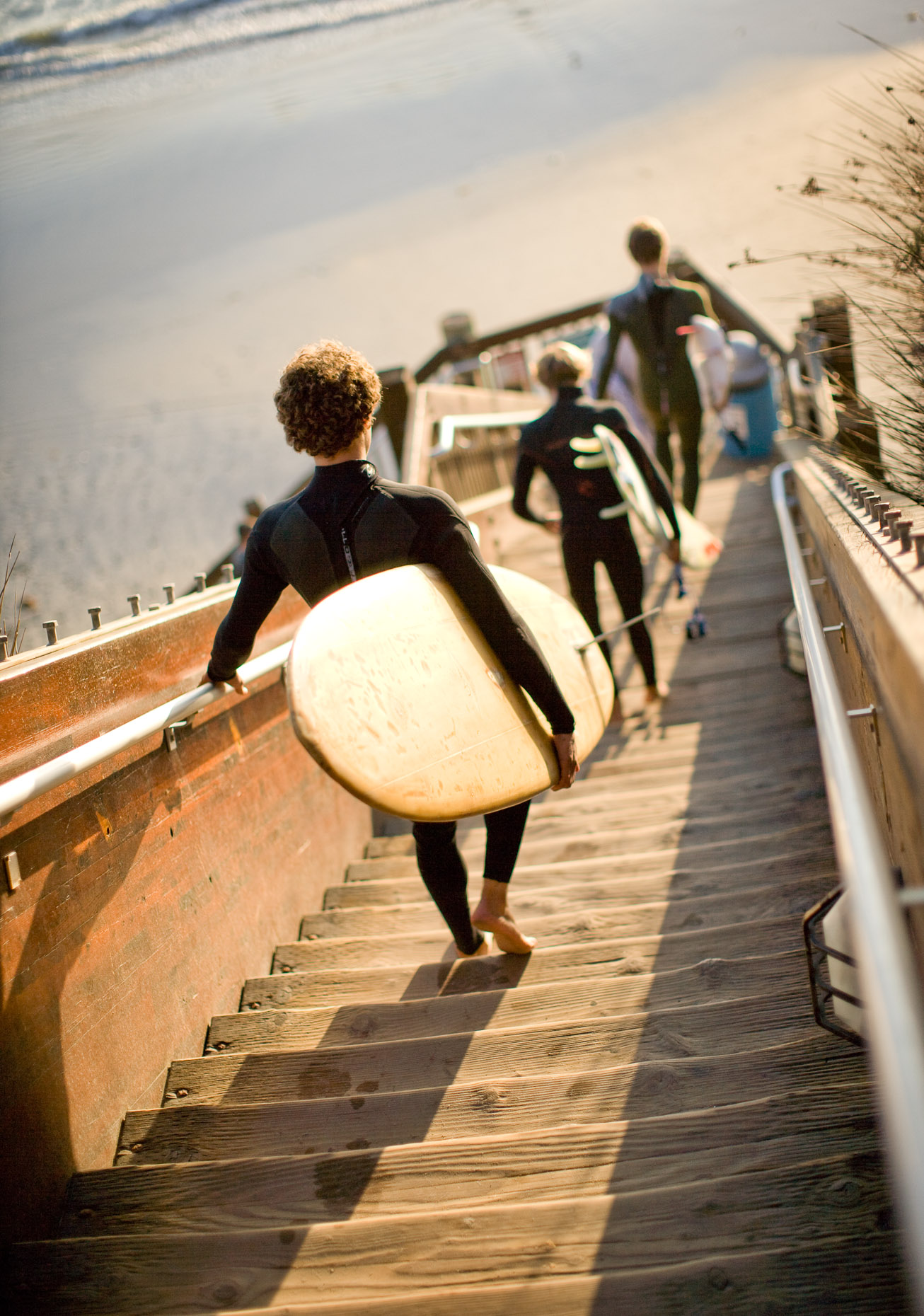 Men in wet suits walking down staircase to beach for surfing by David Zaitz