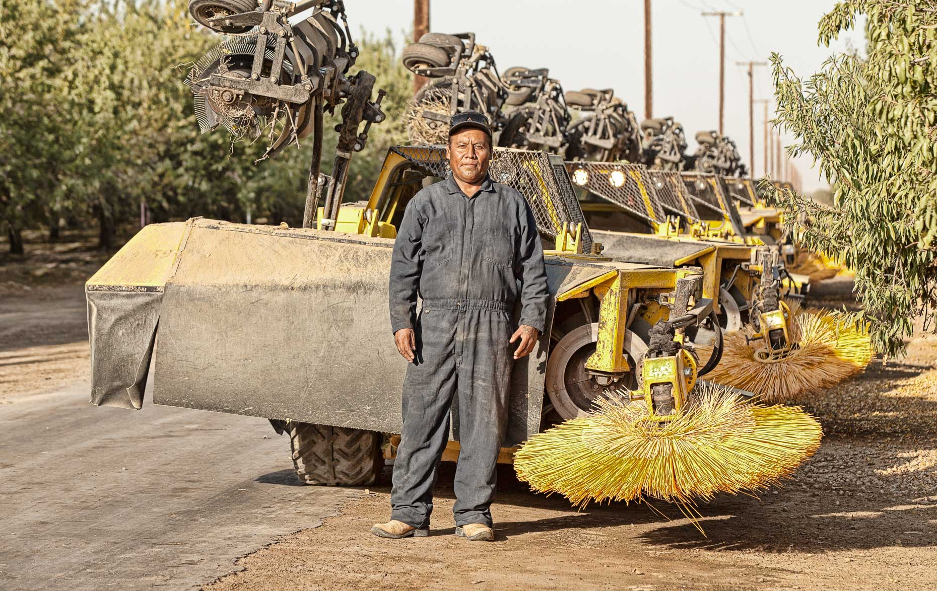 Portrait of farm orchard worker standing in front of sweeper machine in almond orchard near Lost Hills, California by David Zaitz