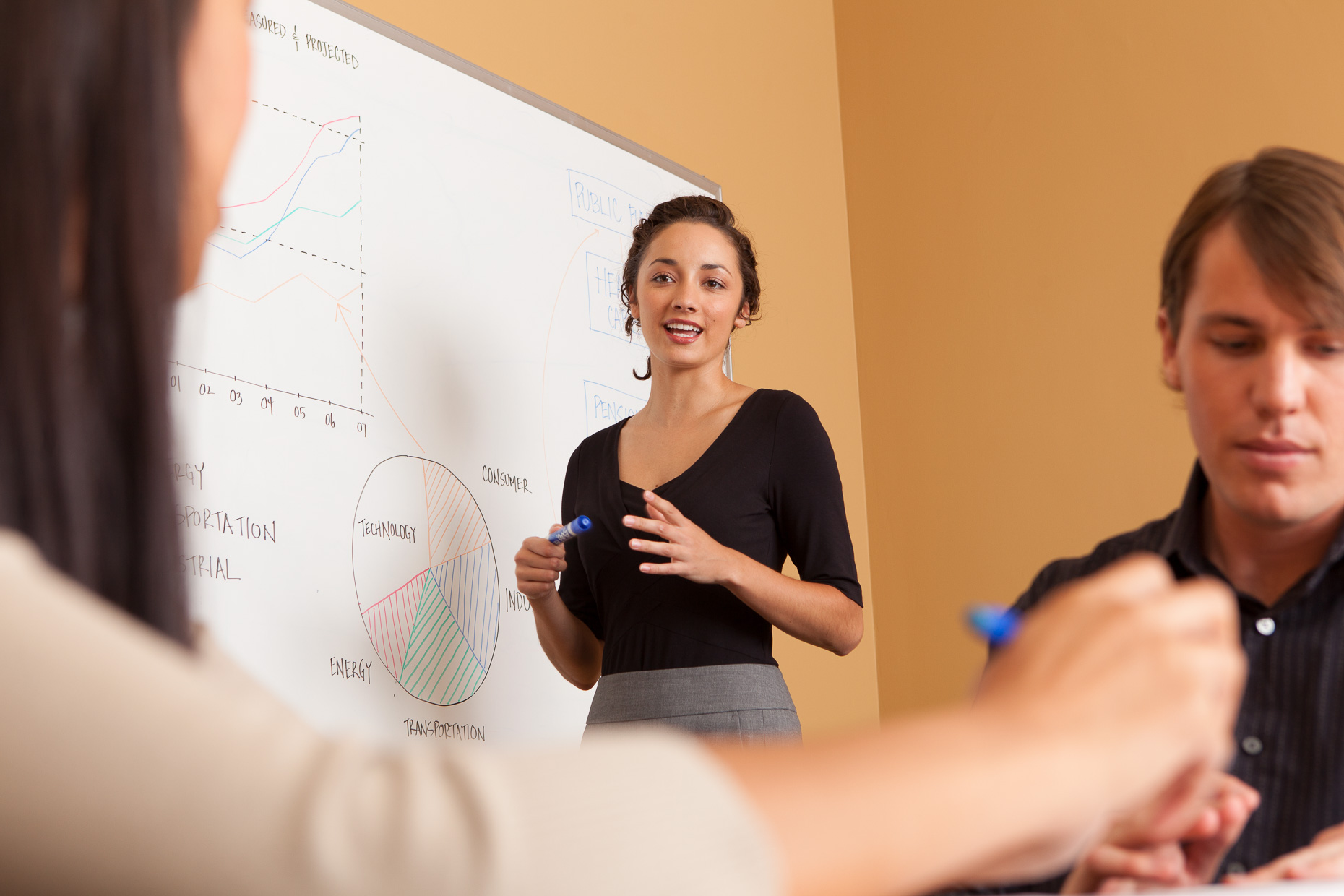 Woman standing next to white board during office meeting in conference room. Corporate. David Zaitz Photography.