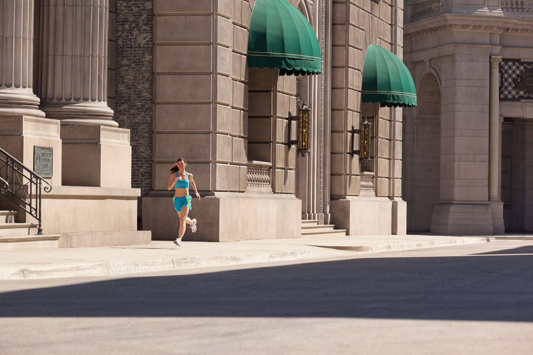 Woman in blue running clothing runs on city street with buildings in background. Fitness. David Zaitz Photography.