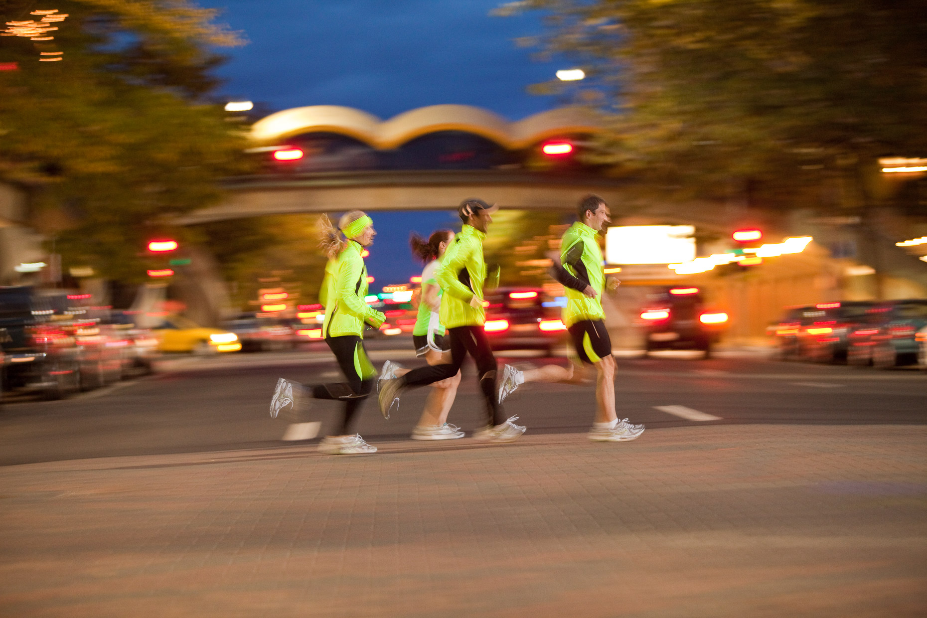 Group of runners with reflective clothing running at night on city street. Spokane, Washington. Fitness. David Zaitz Photography.