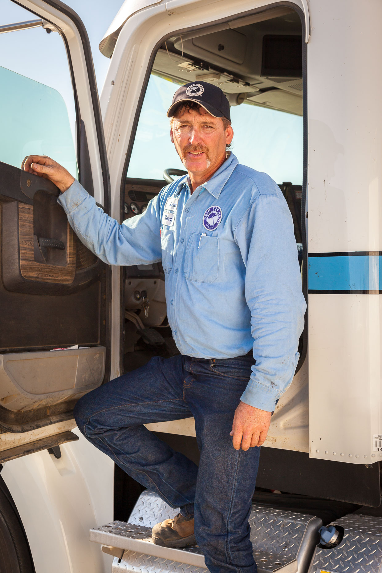 Environmental portrait of truck driver standing in open truck cab by David Zaitz