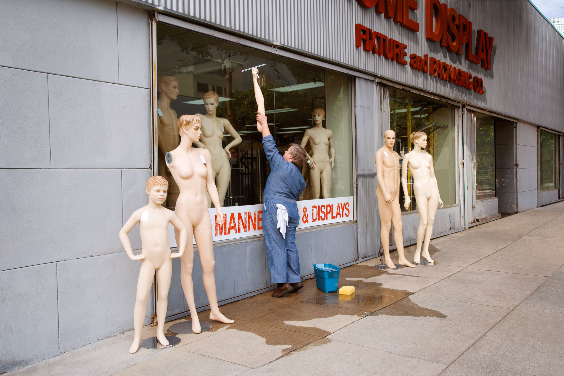 Man washing store windows uses mannequin arm to reach high. David Zaitz