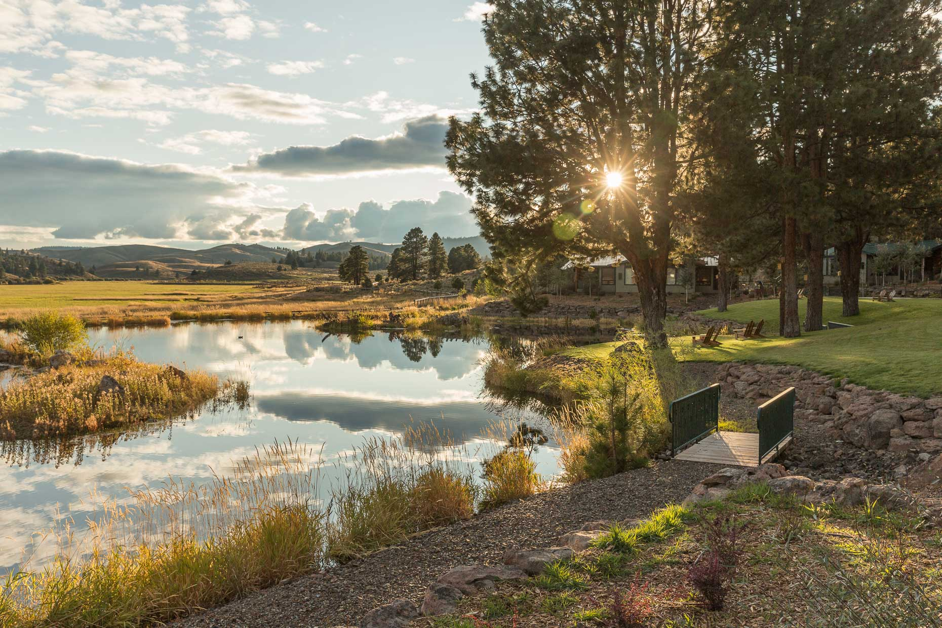 Sunset over pond at Silvies Valley Ranch with bridge, lawn chairs, trees, David Zaitz