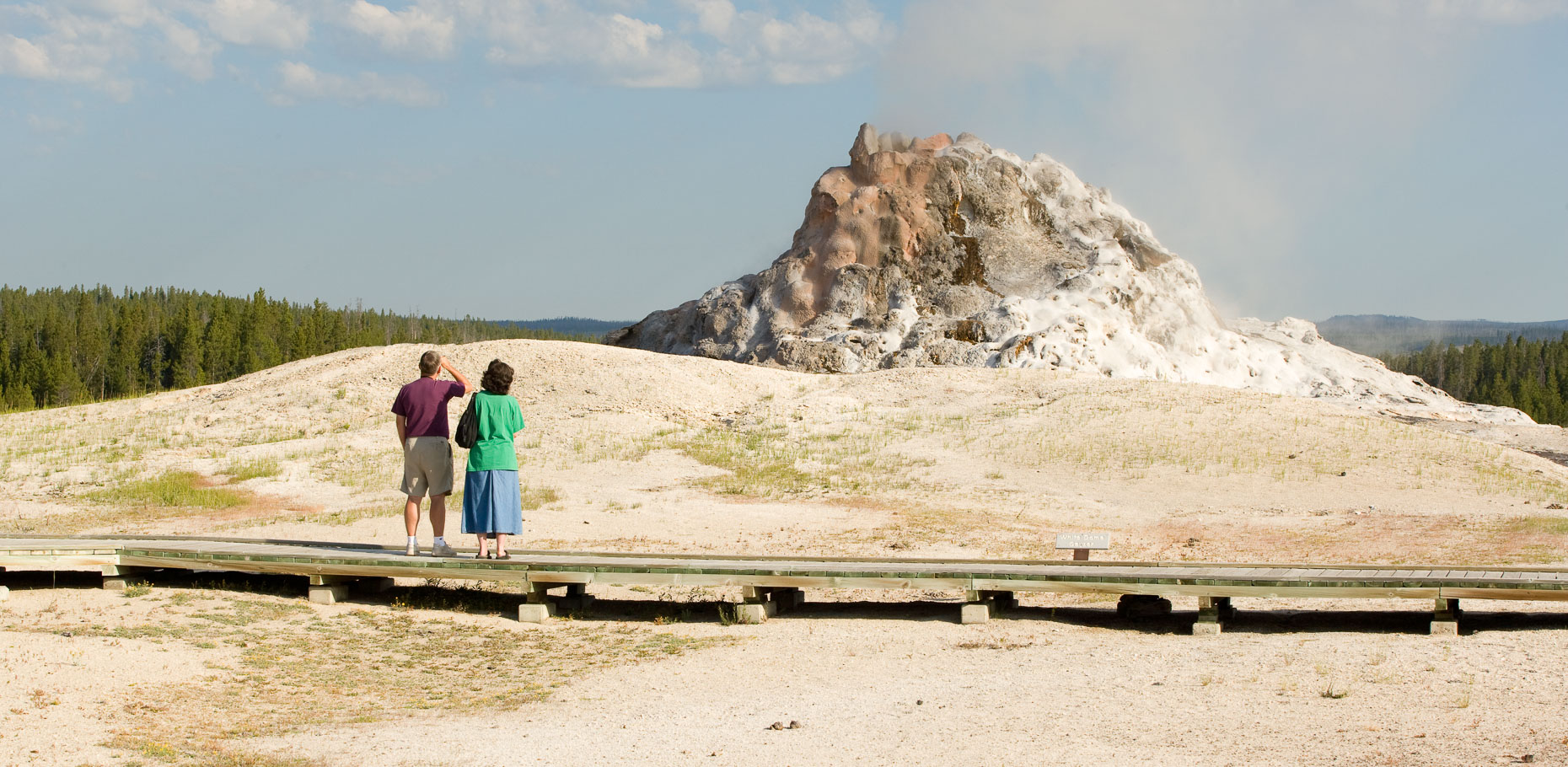 Man and woman standing on boardwalk waiting for geological geyser to erupt in Yellowstone National Park by David Zaitz