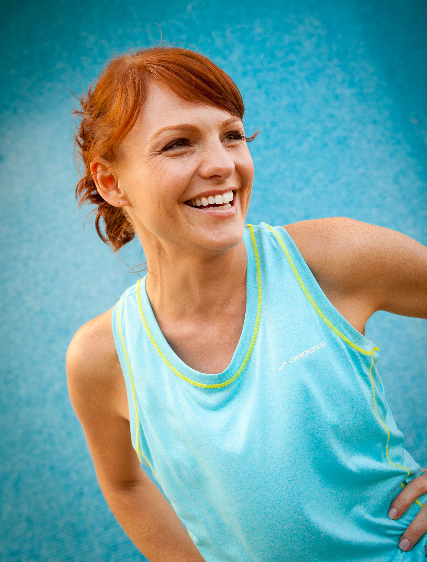 Woman dressed in blue with red hair resting during work out by David Zaitz Photography.