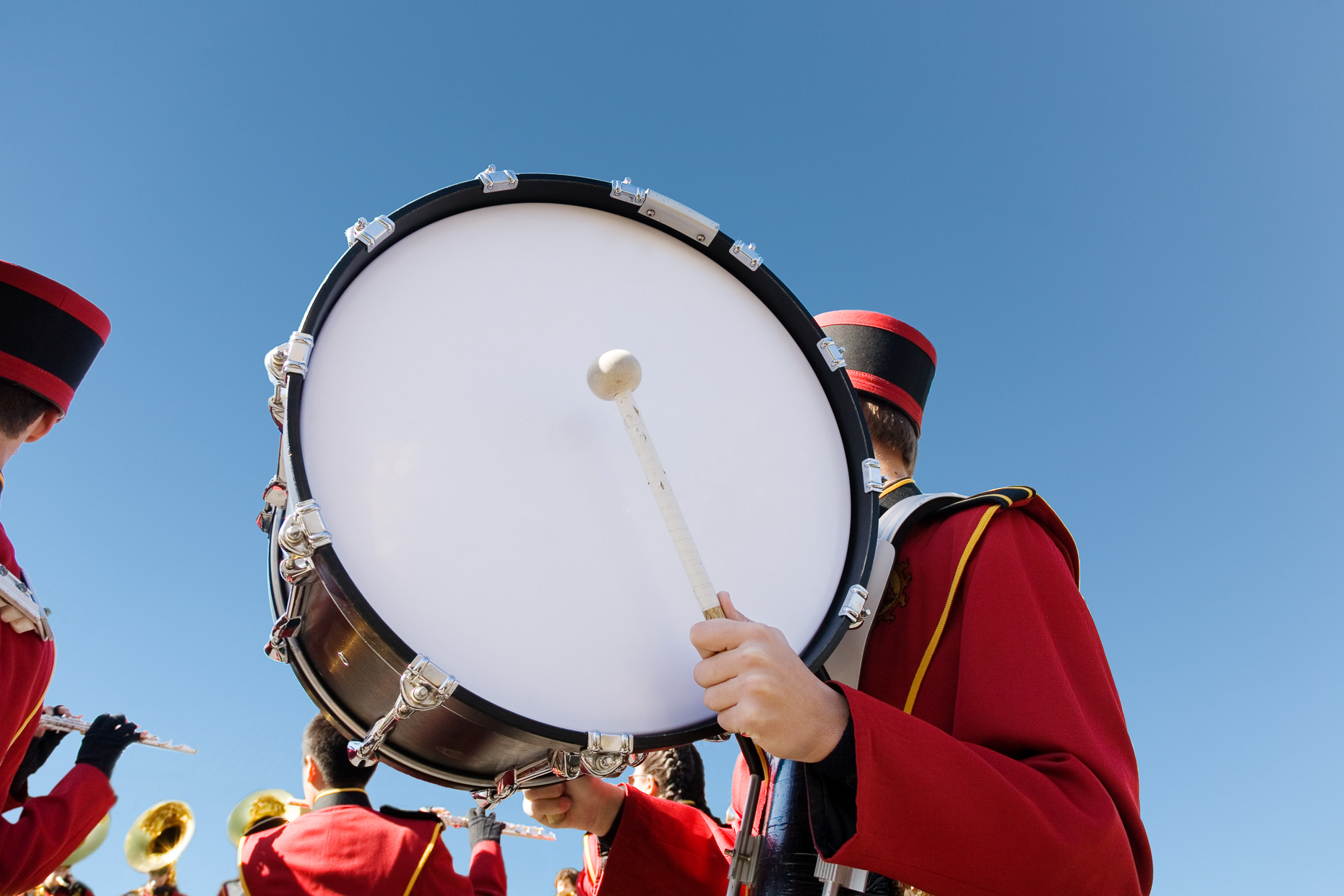 Bass drum of marching band being held by band member in uniform against blue sky by David Zaitz