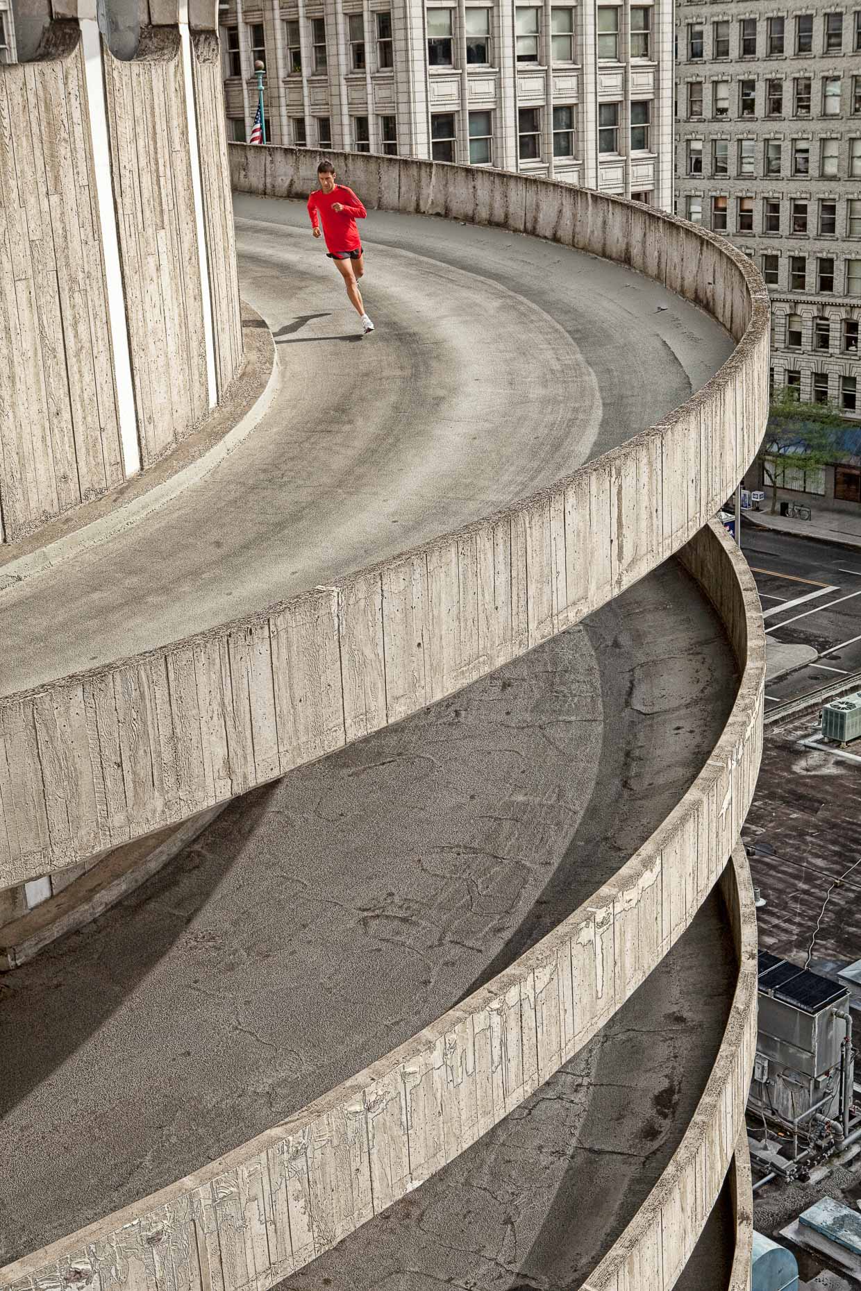 Man running on spiral concrete ramp of multi level parking garage in Spokane, Washington. Fitness. David Zaitz Photography.