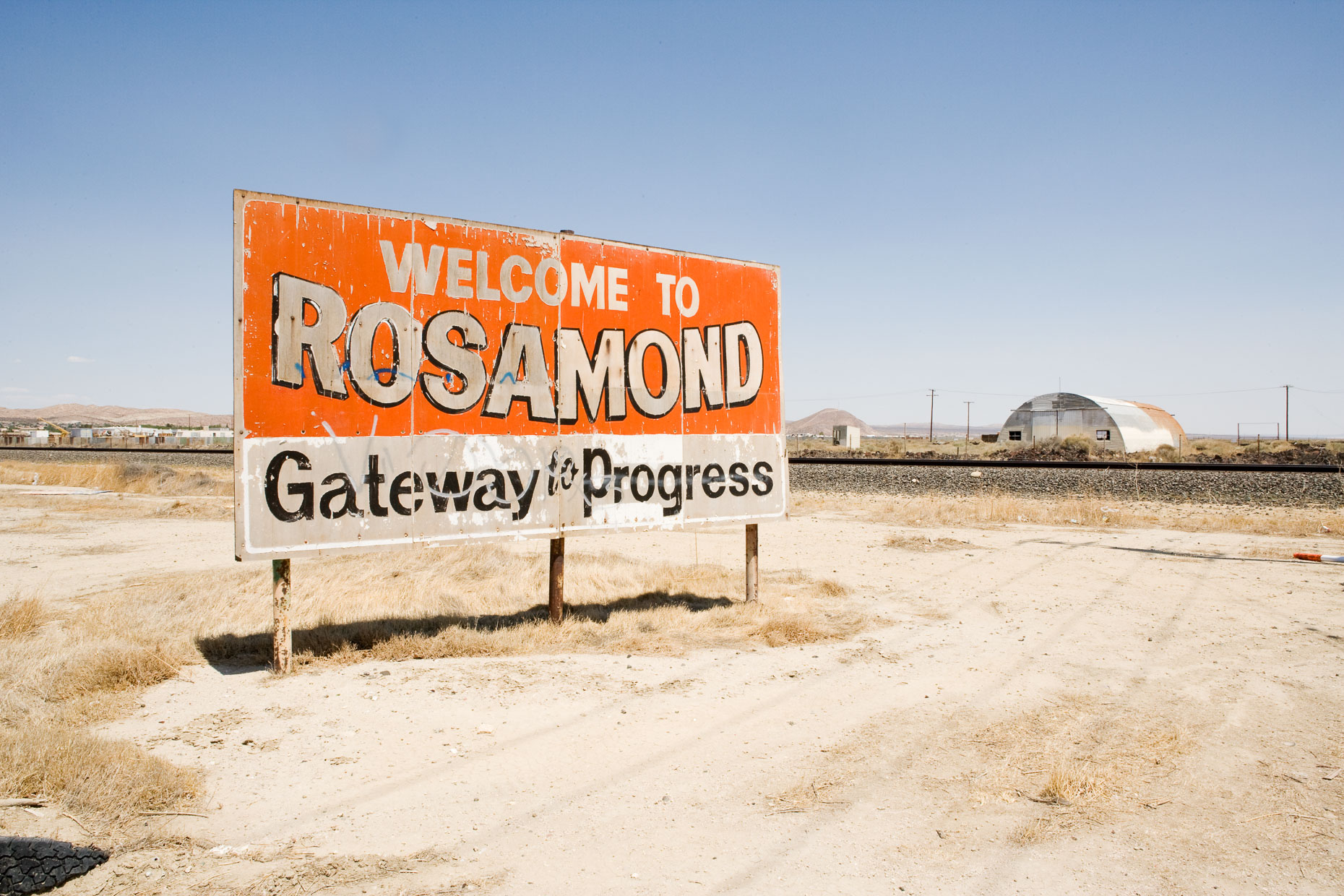 Weathered WELCOME TO ROSAMOND GATEWAY TO PROGRESS billboard on road in desert. Rosamond, California by David Zaitz