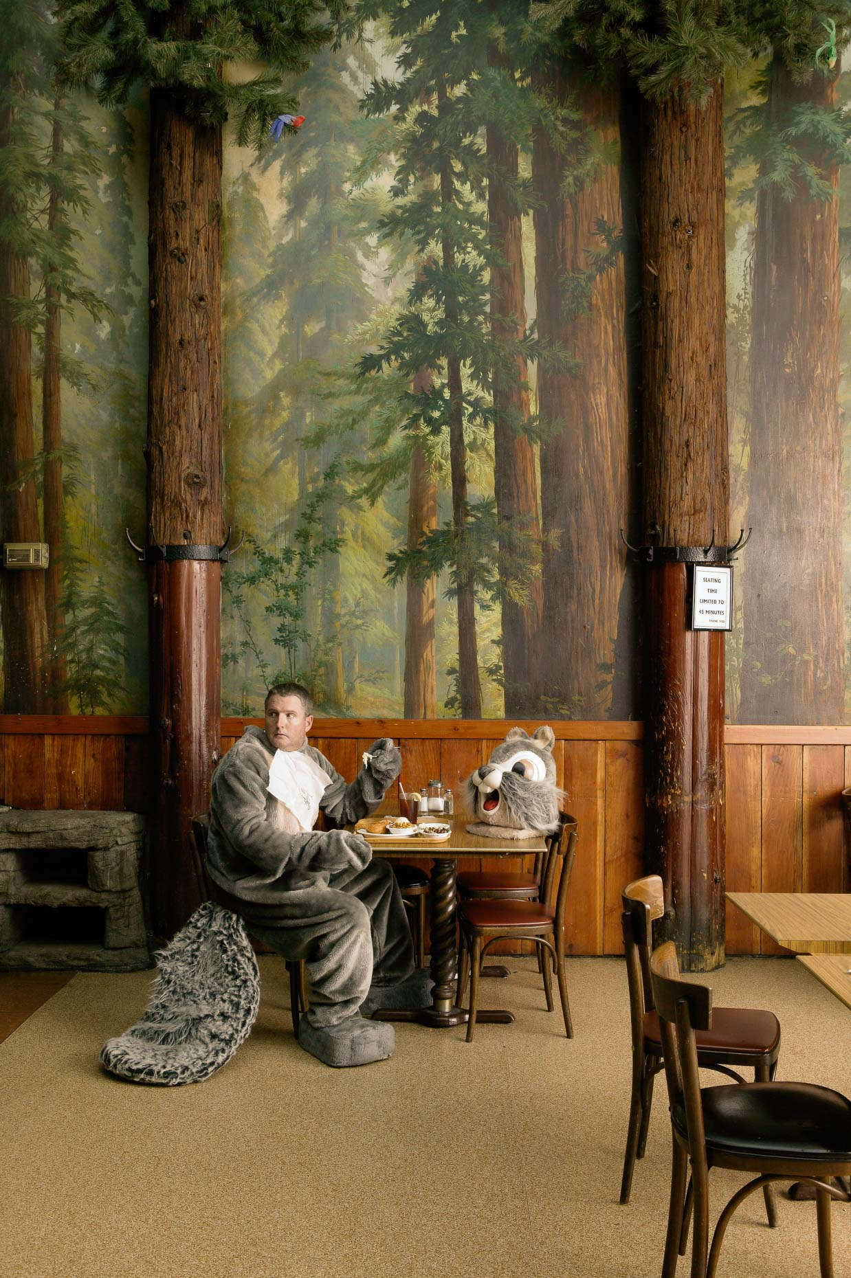Man in squirrel costume having coffee in forest themed restaurant. David Zaitz.