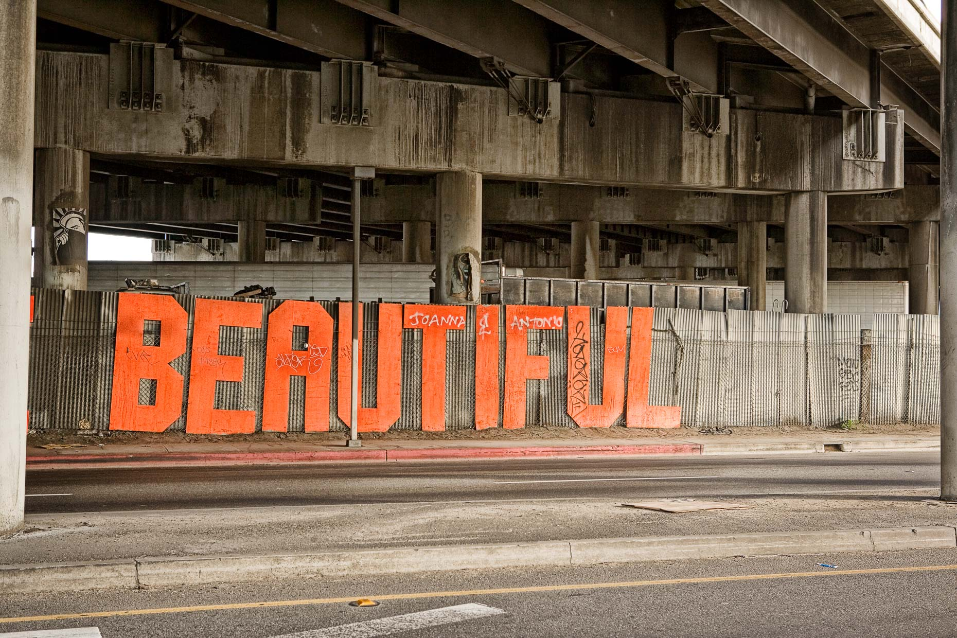 YOU ARE BEAUTIFUL sign is dirty, hanging on fence under freeway overpass in Los Angeles, California by David Zaitz