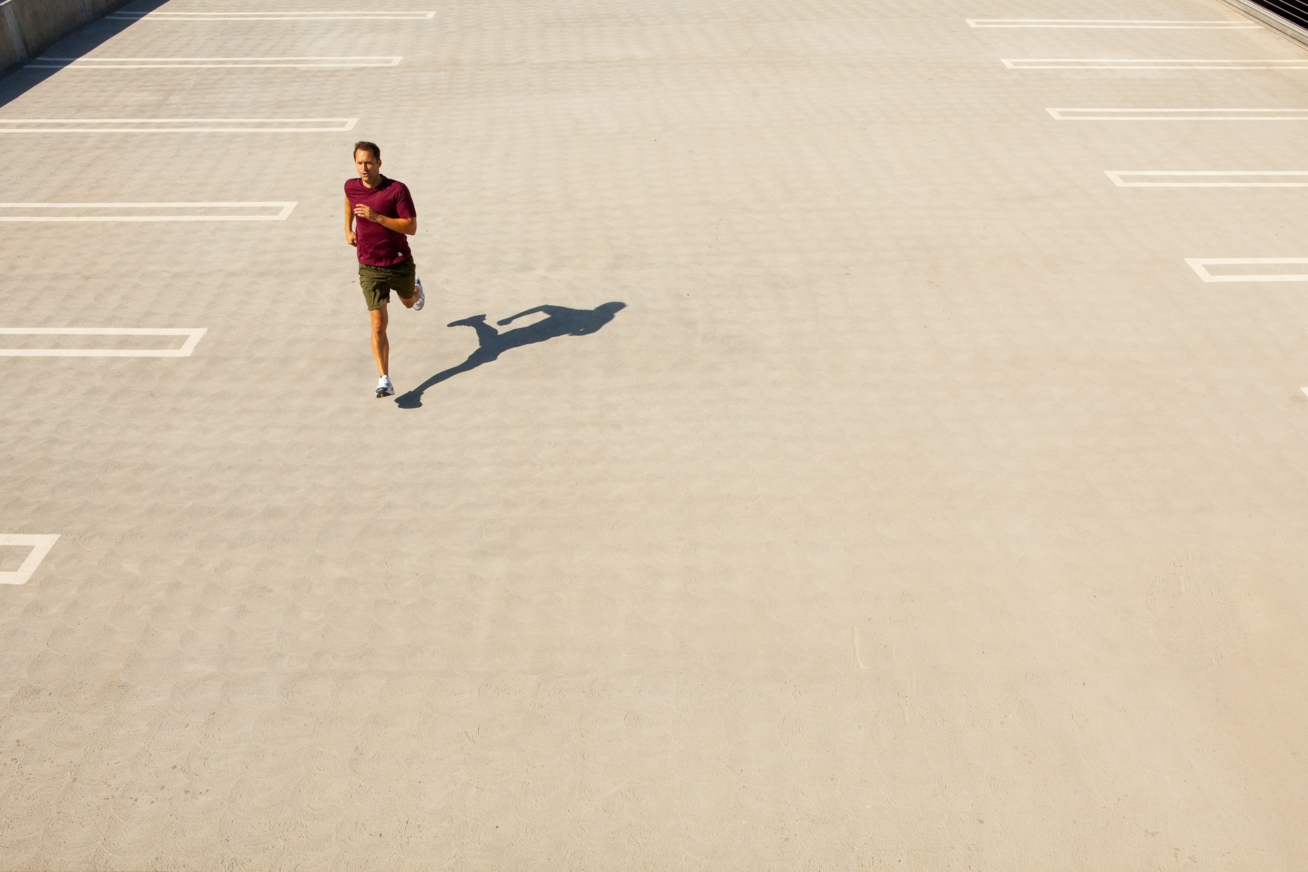 Man running on concrete paved parking lot, aerial by David Zaitz Photography.
