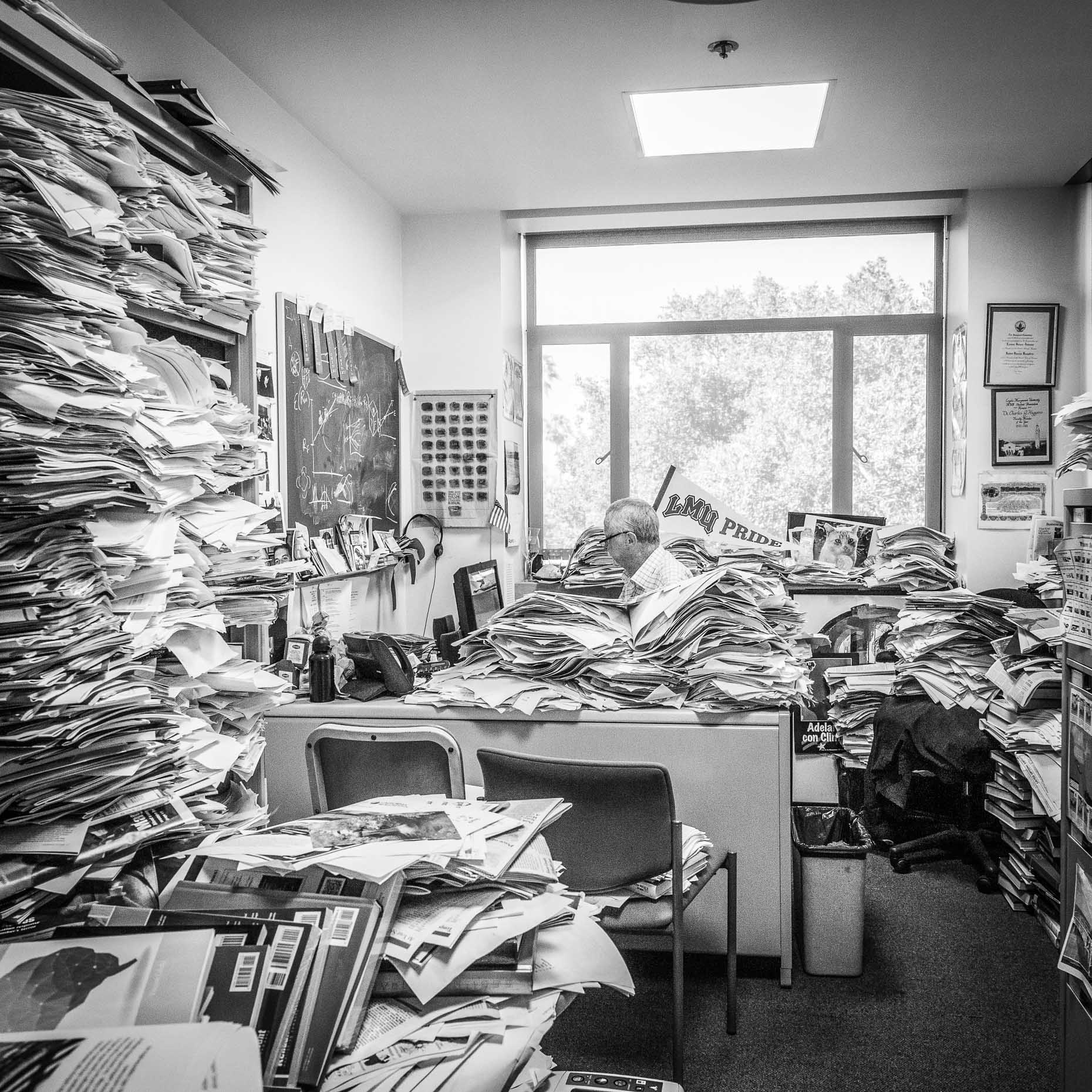 Black and white shot of man in office with many stacks of paper and folders by David Zaitz