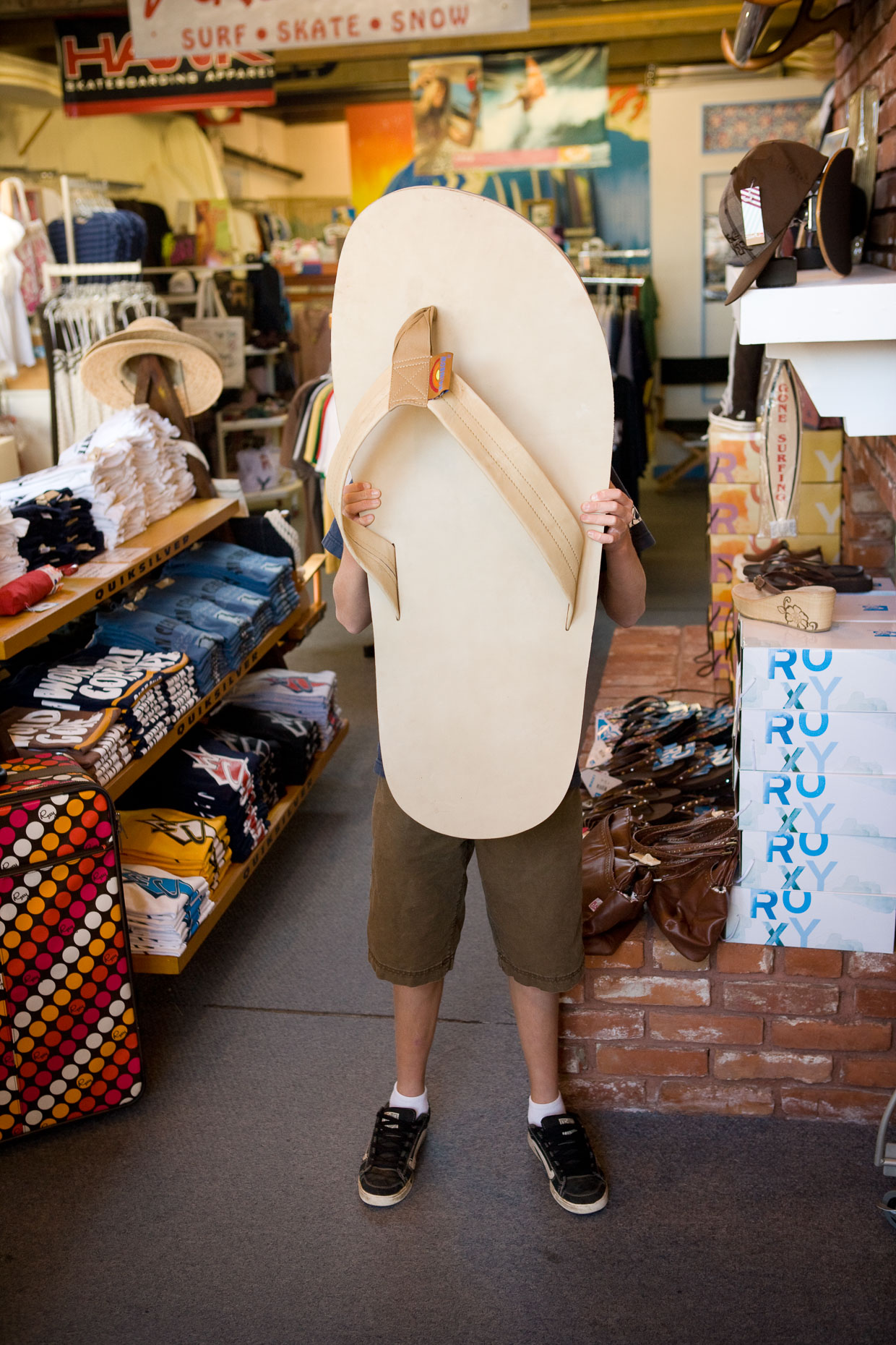 Boy holds oversized large sandal over his face in retail store in Seal Beach, California by David Zaitz