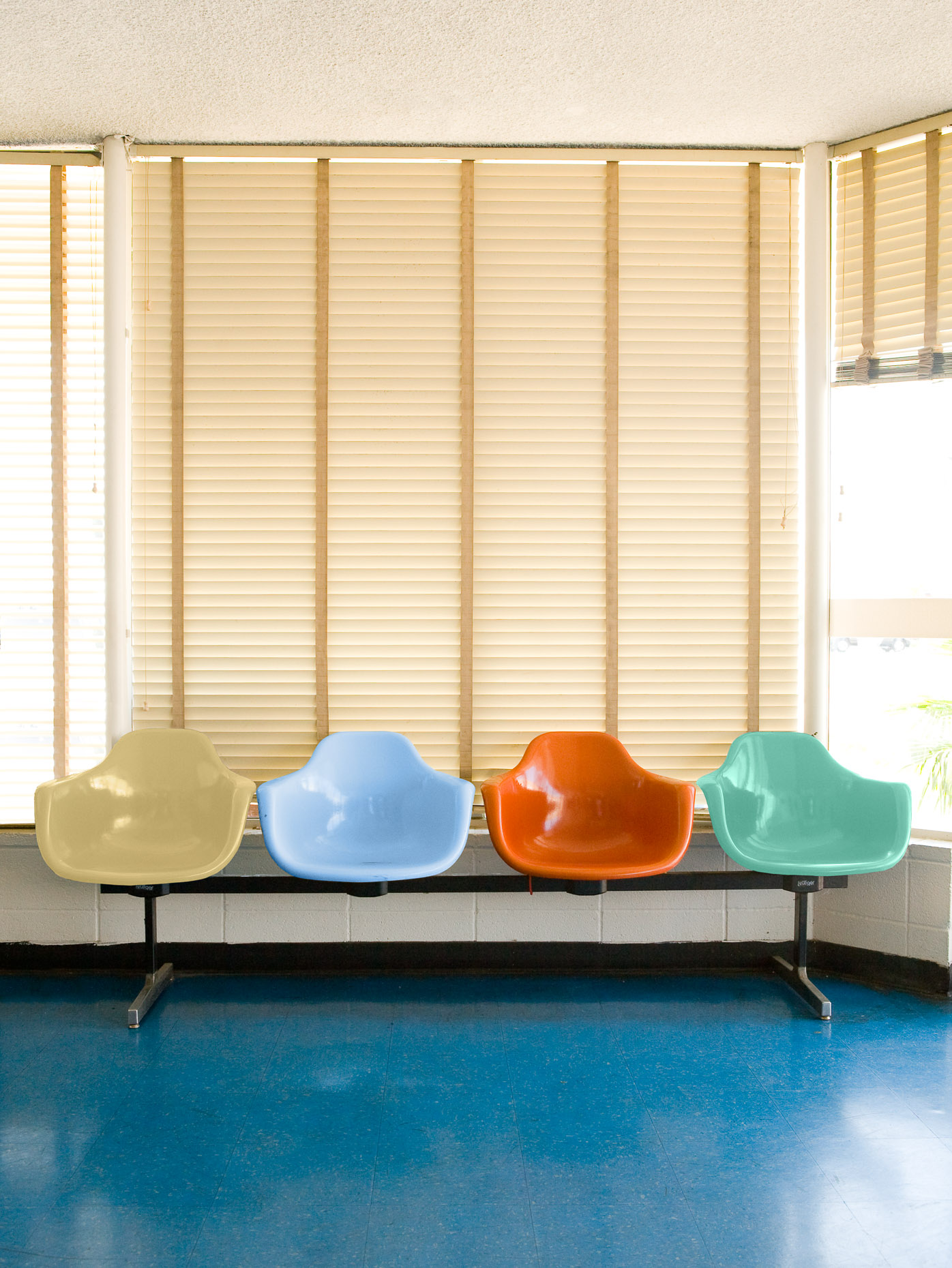 Moulded plastic chairs in a row creating seating in a bus station waiting room with Venetian blinds by David Zaitz