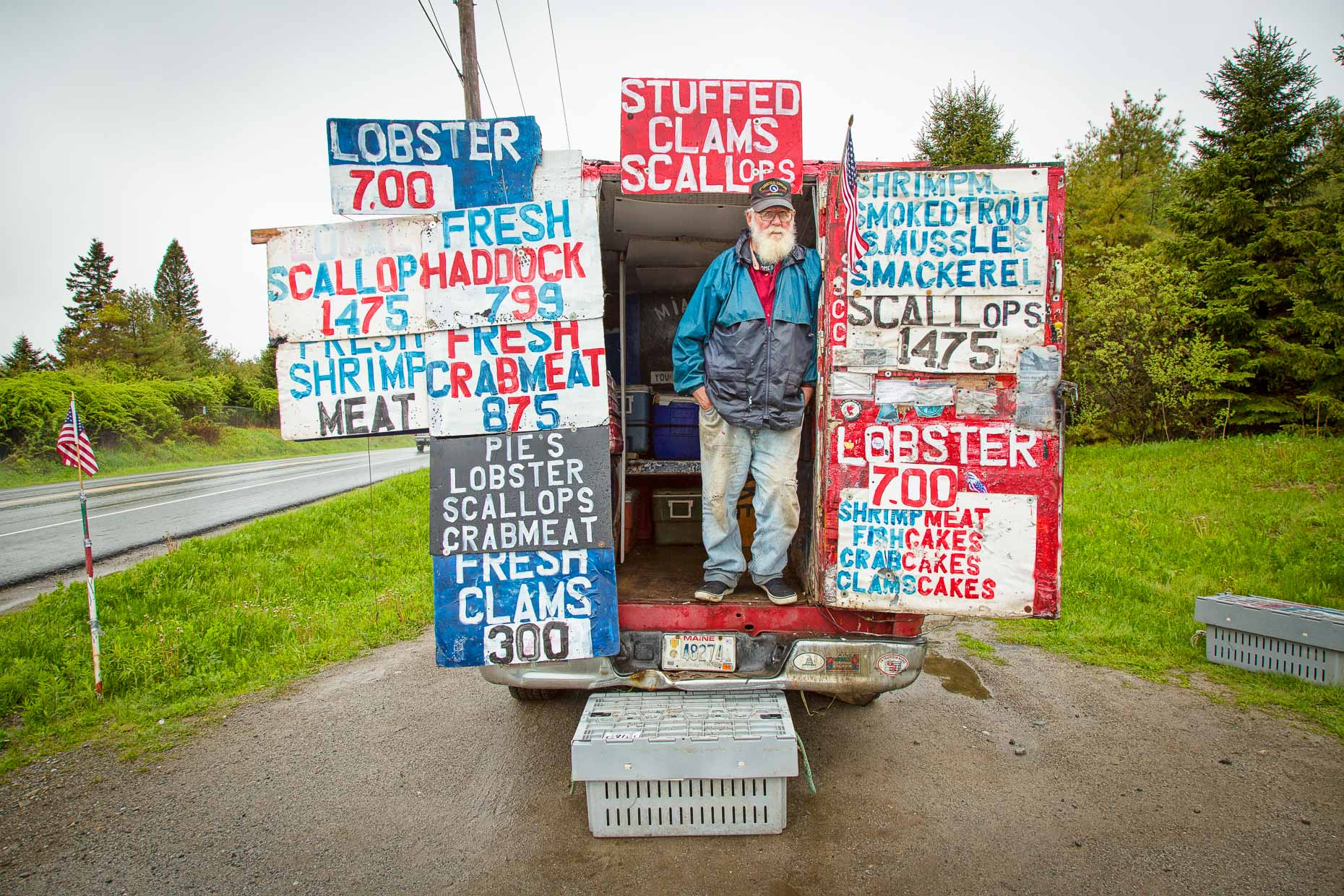 Environmental portrait of man selling fish out of truck parked along road with colorful signage in Maine by David Zaitz