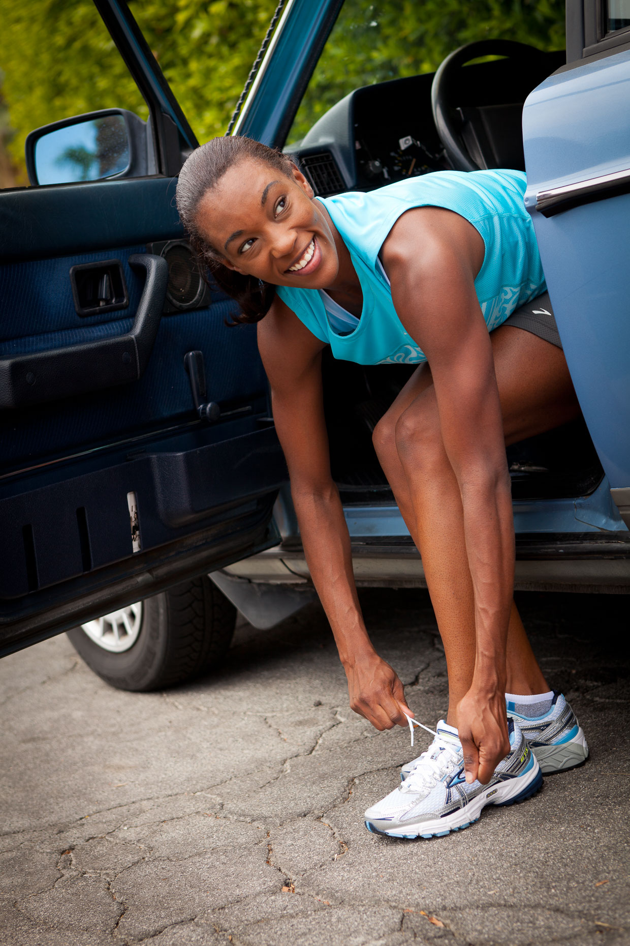 African American woman sitting in car with feet on ground tying shoe before fitness run exercise. Palm Springs, California. David Zaitz Photography.