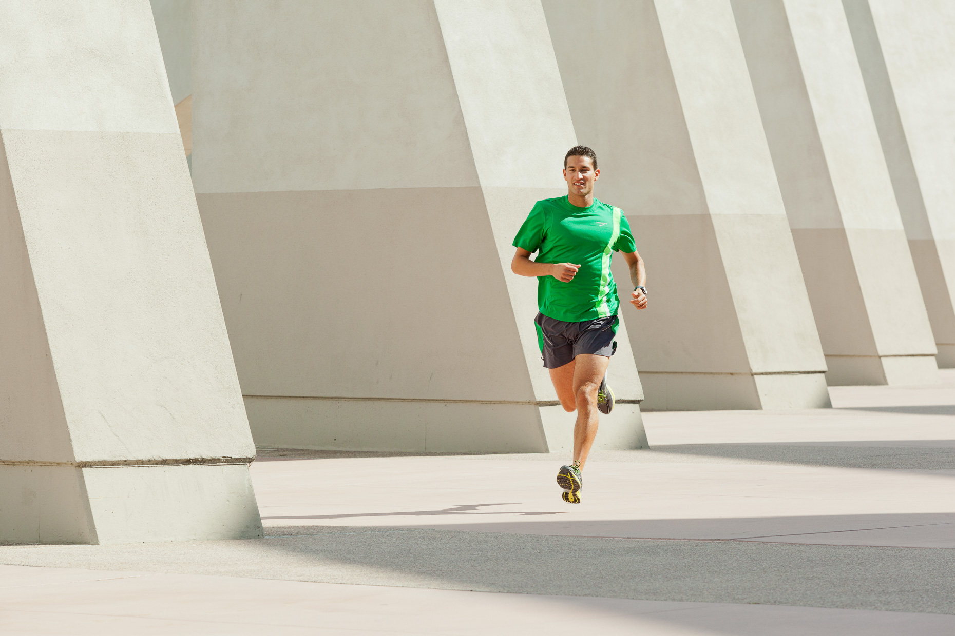 Man running with concrete diagonal structure in background. San Diego, California. Fitness by David Zaitz Photography.